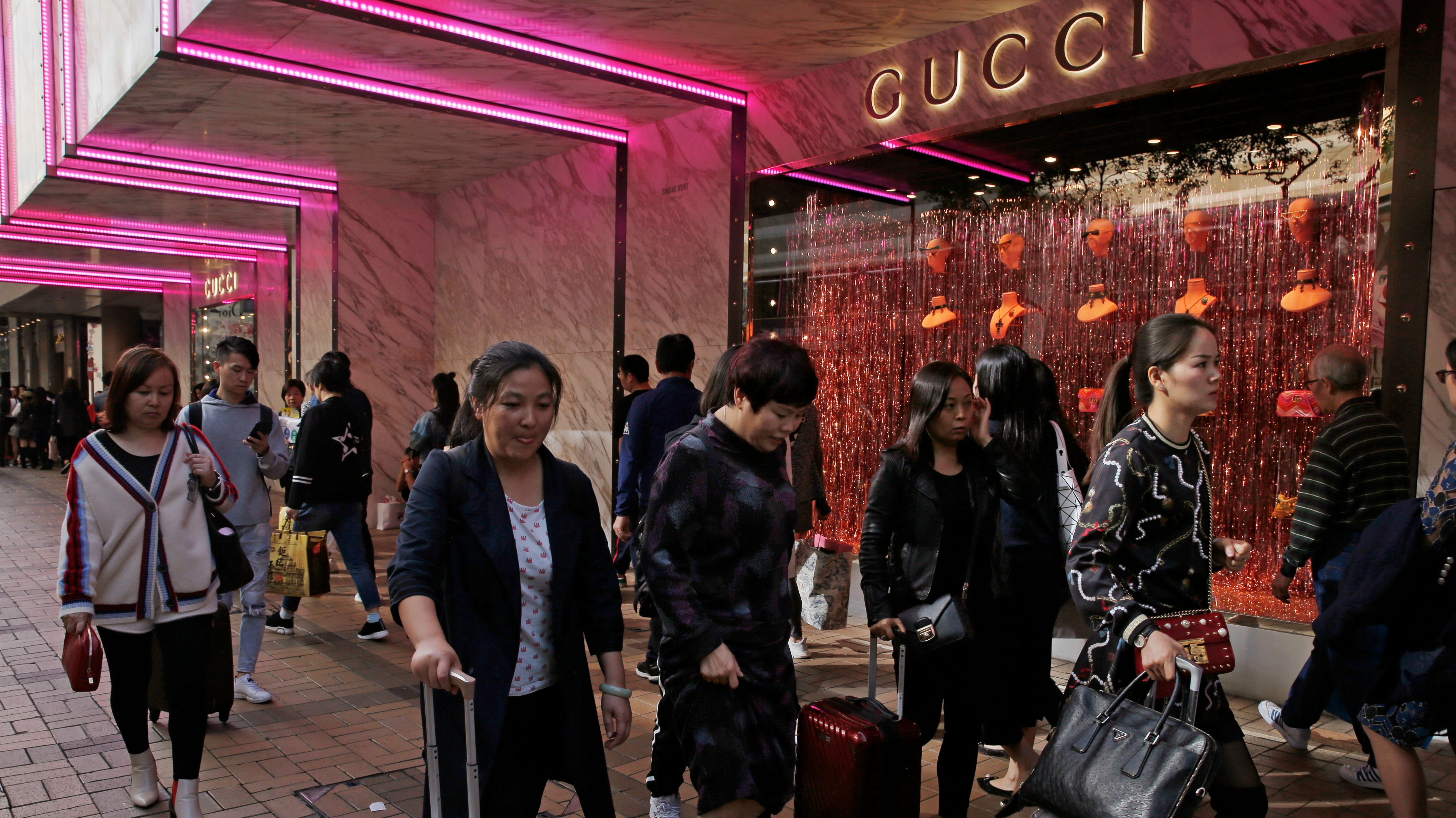 In this Thursday, Nov. 29, 2018, photo, Chinese tourists walk on the Canton Road, the one-stop-shop high street of high-end brands in Hong Kong. Chinese tourists, big customers for global luxury retailers, are skittish after a year marked by cooling economic growth, a plunge in stock prices, trade tension with Washington and a soft real estate market. (AP Photo/Kin Cheung)