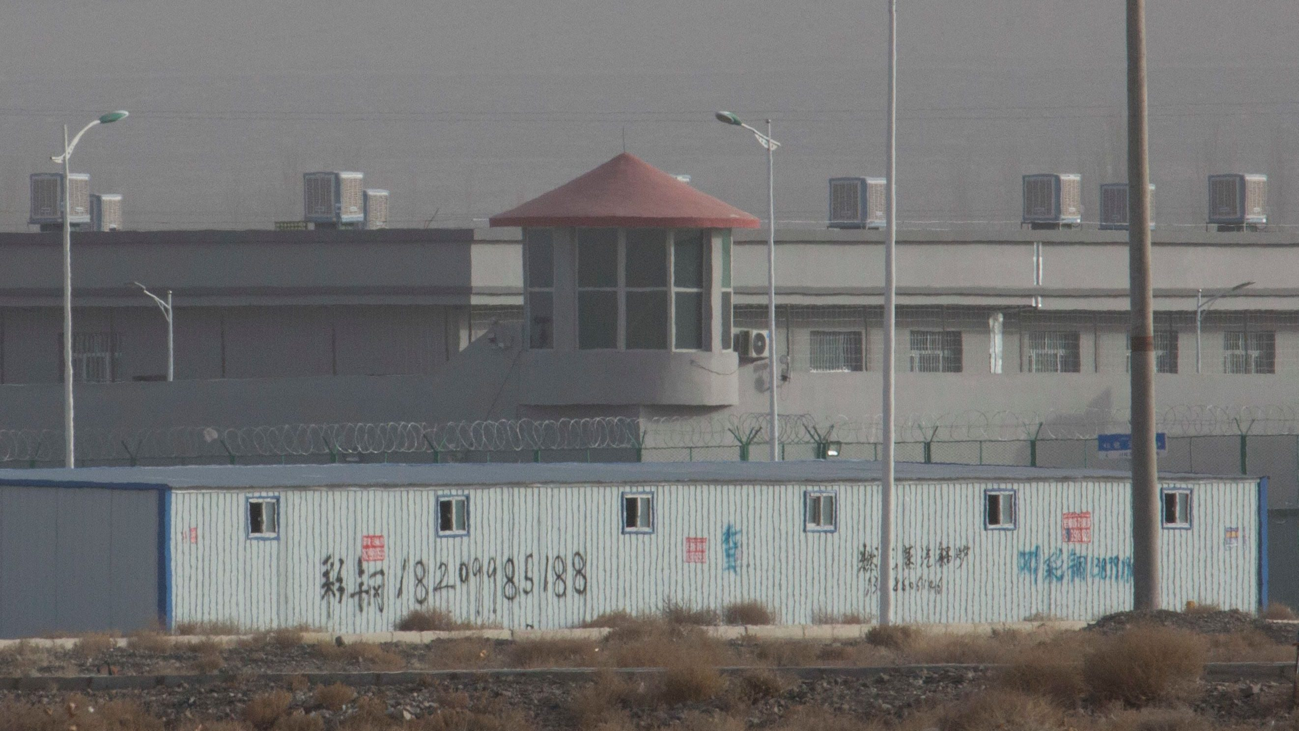 In this Monday, Dec. 3, 2018, photo, a guard tower and barbed wire fences are seen around a facility in the Kunshan Industrial Park in Artux in western China's Xinjiang region. This is one of a growing number of internment camps in the Xinjiang region, where by some estimates 1 million Muslims are detained, forced to give up their language and their religion and subject to political indoctrination. Now, the Chinese government is also forcing some detainees to work in manufacturing and food industries. Some of them are within the internment camps; others are privately owned, state-subsidized factories where detainees are sent once they are released. (AP Photo/Ng Han Guan)