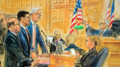 This courtroom sketch depicts former President Donald Trump's former national security adviser Michael Flynn, standing center, flanked by his lawyers, listening to U.S. District Judge Emmet Sullivan, right, as he addresses Flynn and points to the American flag inside the federal court in Washington, Washington, Tuesday, Dec. 18, 2018. Sullivan agreed to postpone Flynn's sentencing so he can continue cooperating with the Russia probe.