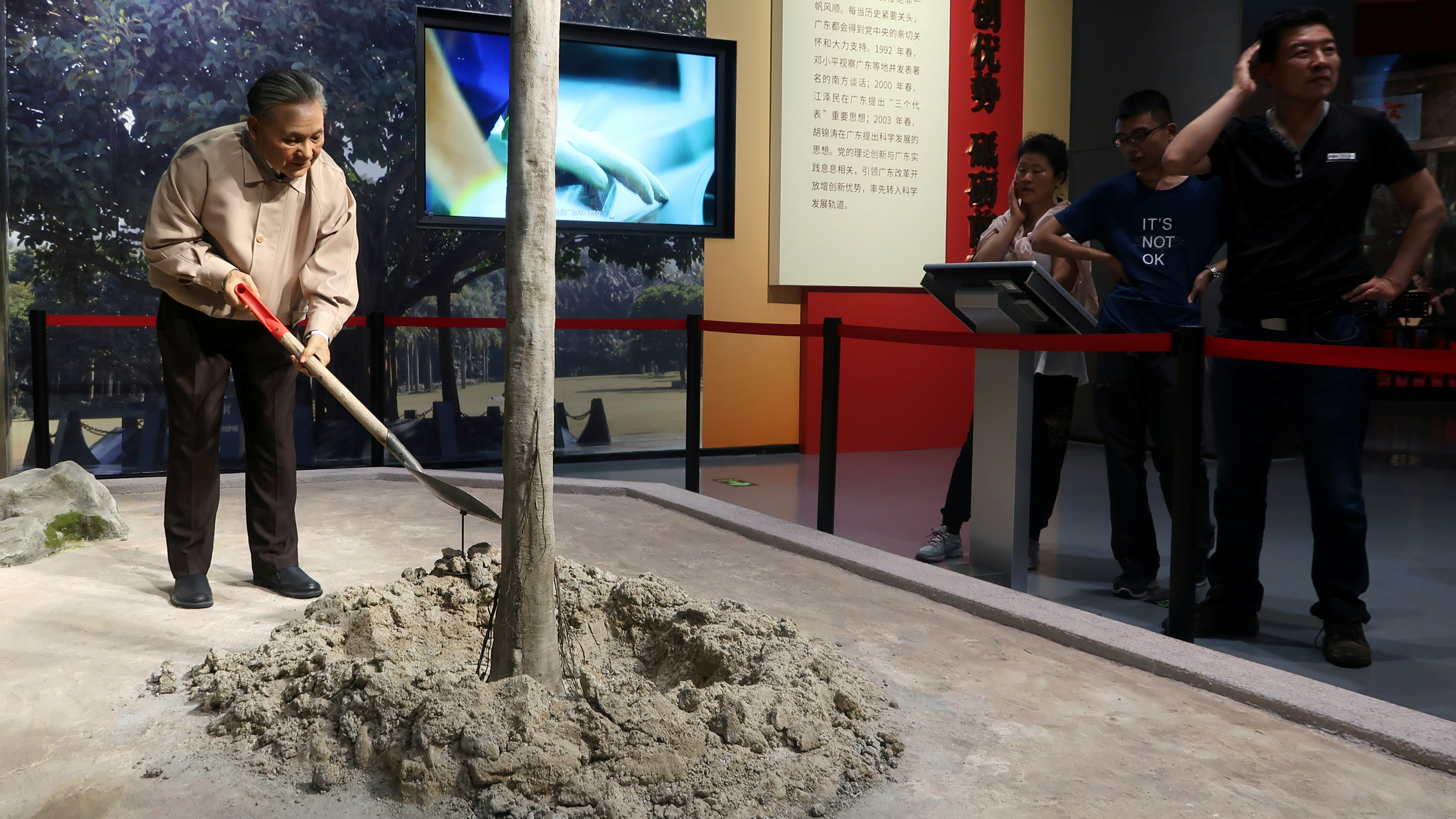 Visitors look at an exhibit showing the former Chinese leader Deng Xiaoping planting a tree.