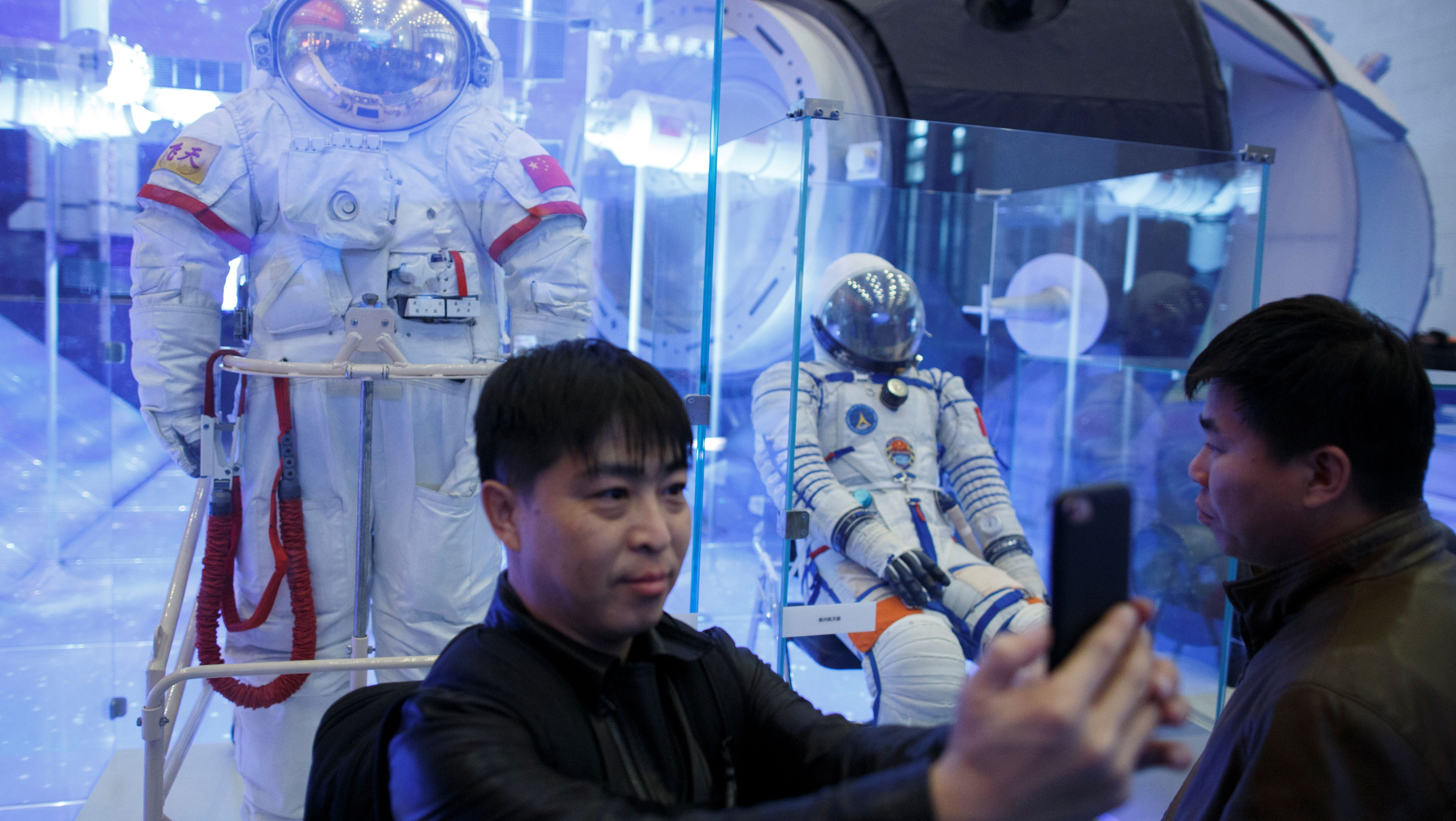 A visitor takes a selfie in front of a Chinese space suit at an exhibition marking the 40th anniversary of China's reform and opening up at the National Museum of China in Beijing, China November 14, 2018. REUTERS/Thomas Peter