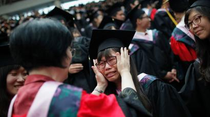 A teacher comforts weeping graduate during graduation ceremony at Fudan University