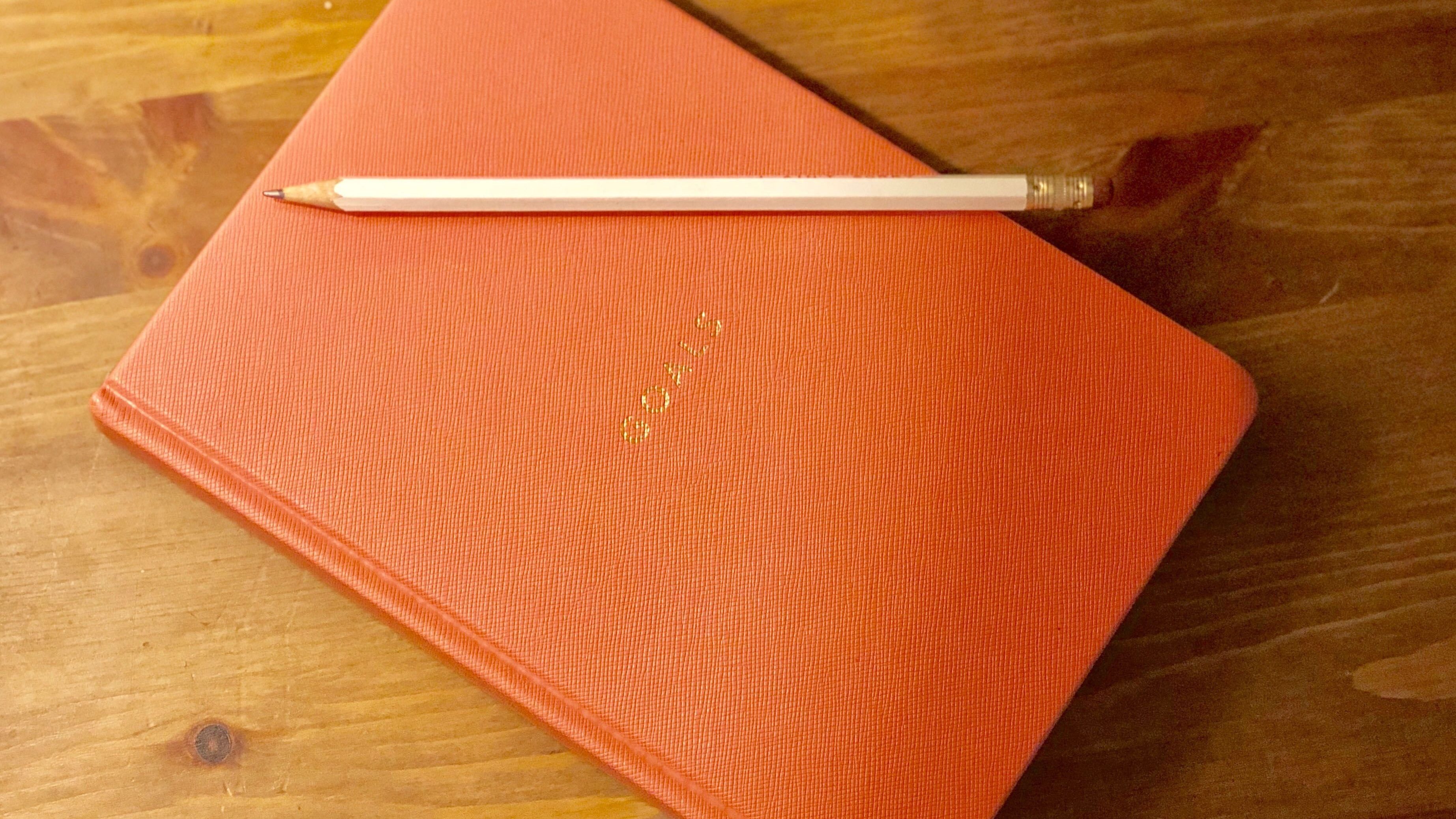 "An image of a pink journal that says ""Goals"" with a white sharpened pencil on top against a wooden background."