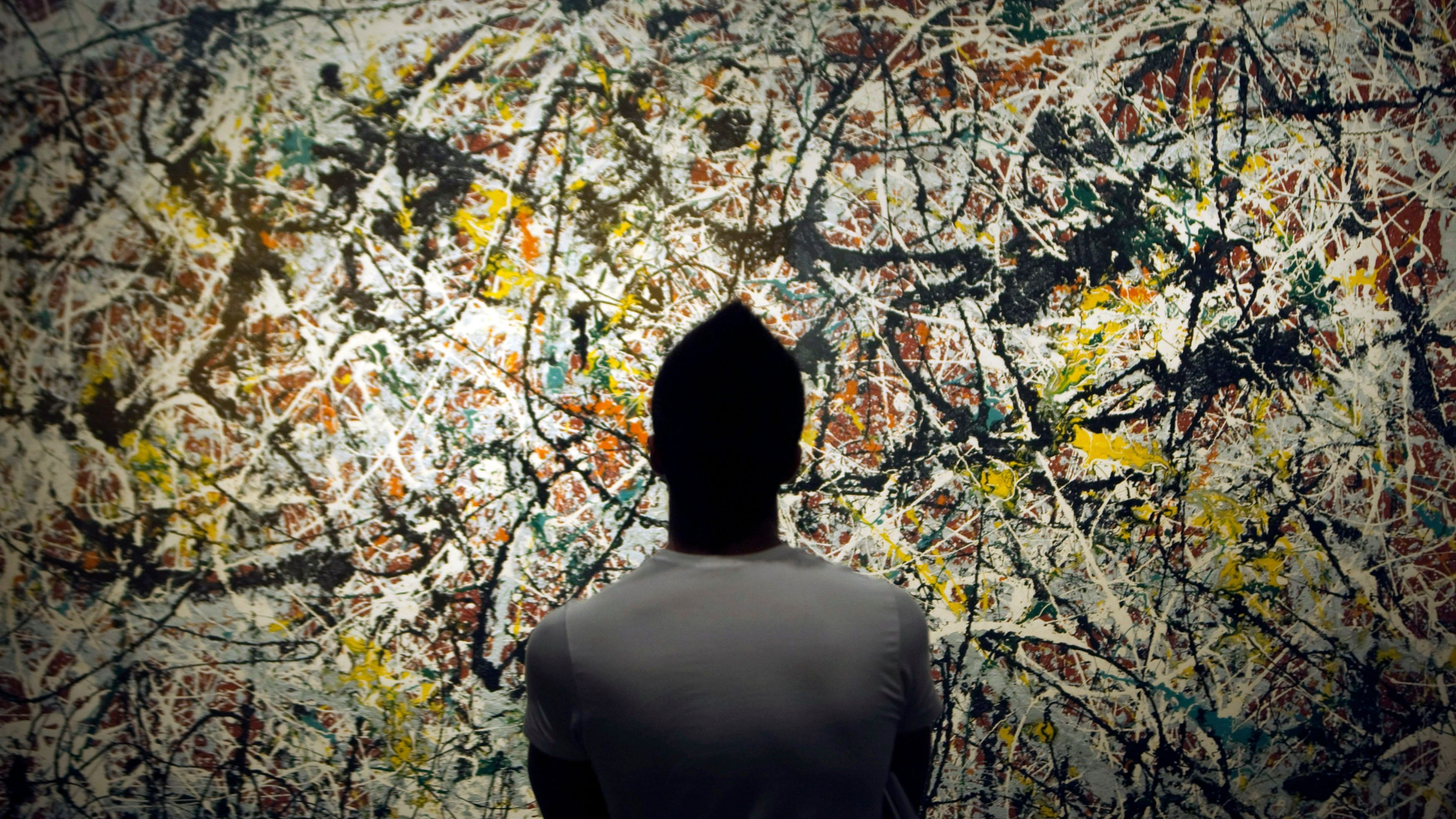 A person looks at a Jackson Pollock painting in an art gallery