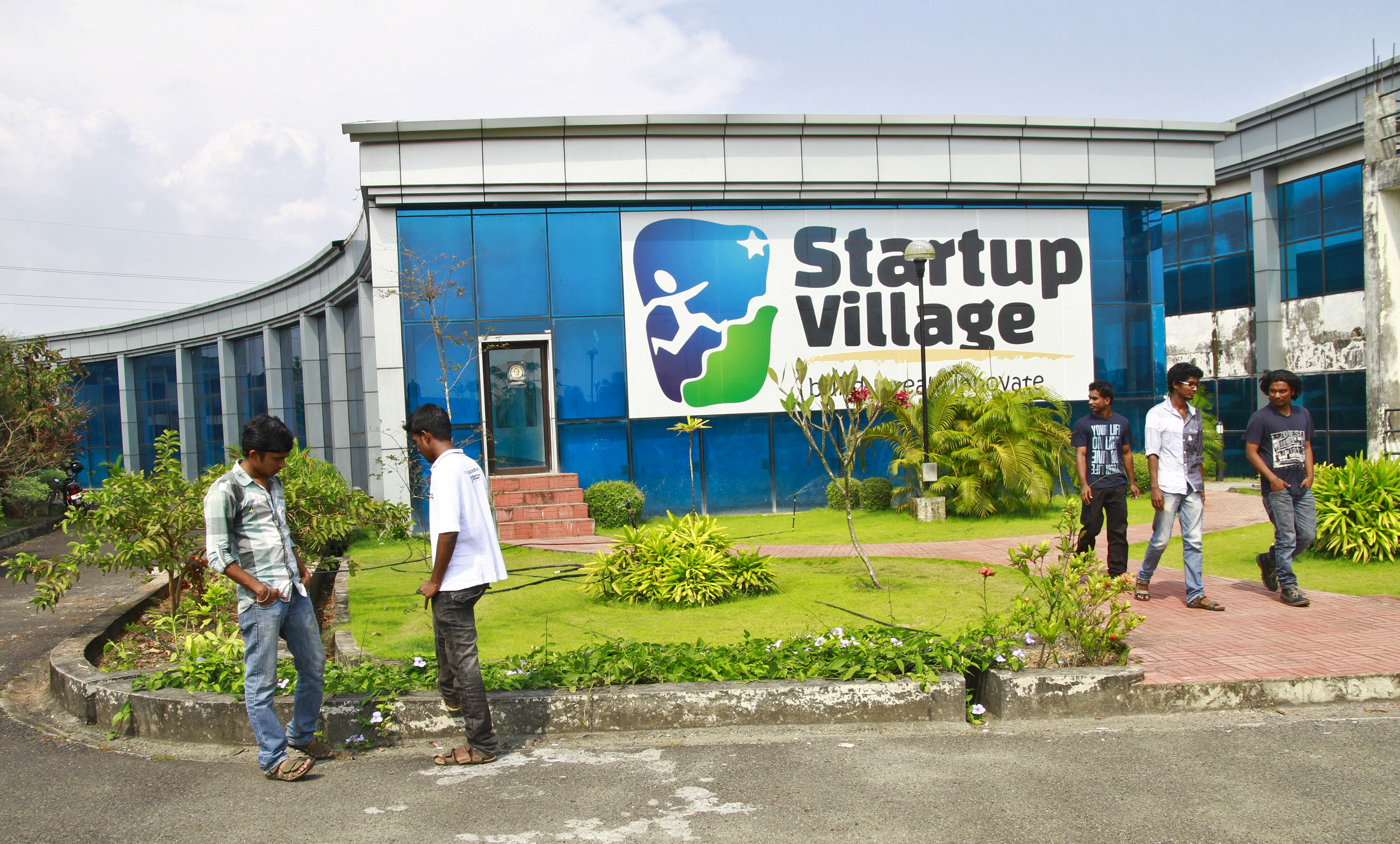 Employees stand outside the Start-up Village in Kinfra High Tech Park in Kochi