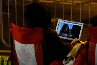 Canadian fans of the royal family watches Meghan Markle in a TV show called 'Suits' as they camp outside Windsor Castle prior to the wedding of Prince Harry and Meghan Markle in Windsor