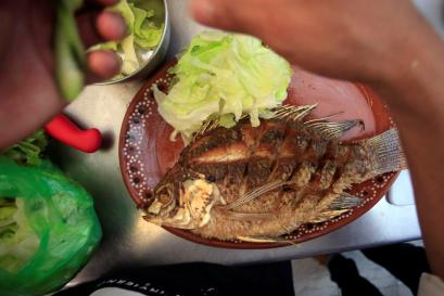 A man prepares a plate of Mojarra fish, also known as Gerreidae, at a seafood restaurant in Monterrey, Mexico
