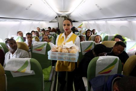 FILE PHOTO: Flight attendant serves passengers with breakfast inside Ethiopian Airlines ET314 flight to Eritrea's capital Asmara, from Addis Ababa