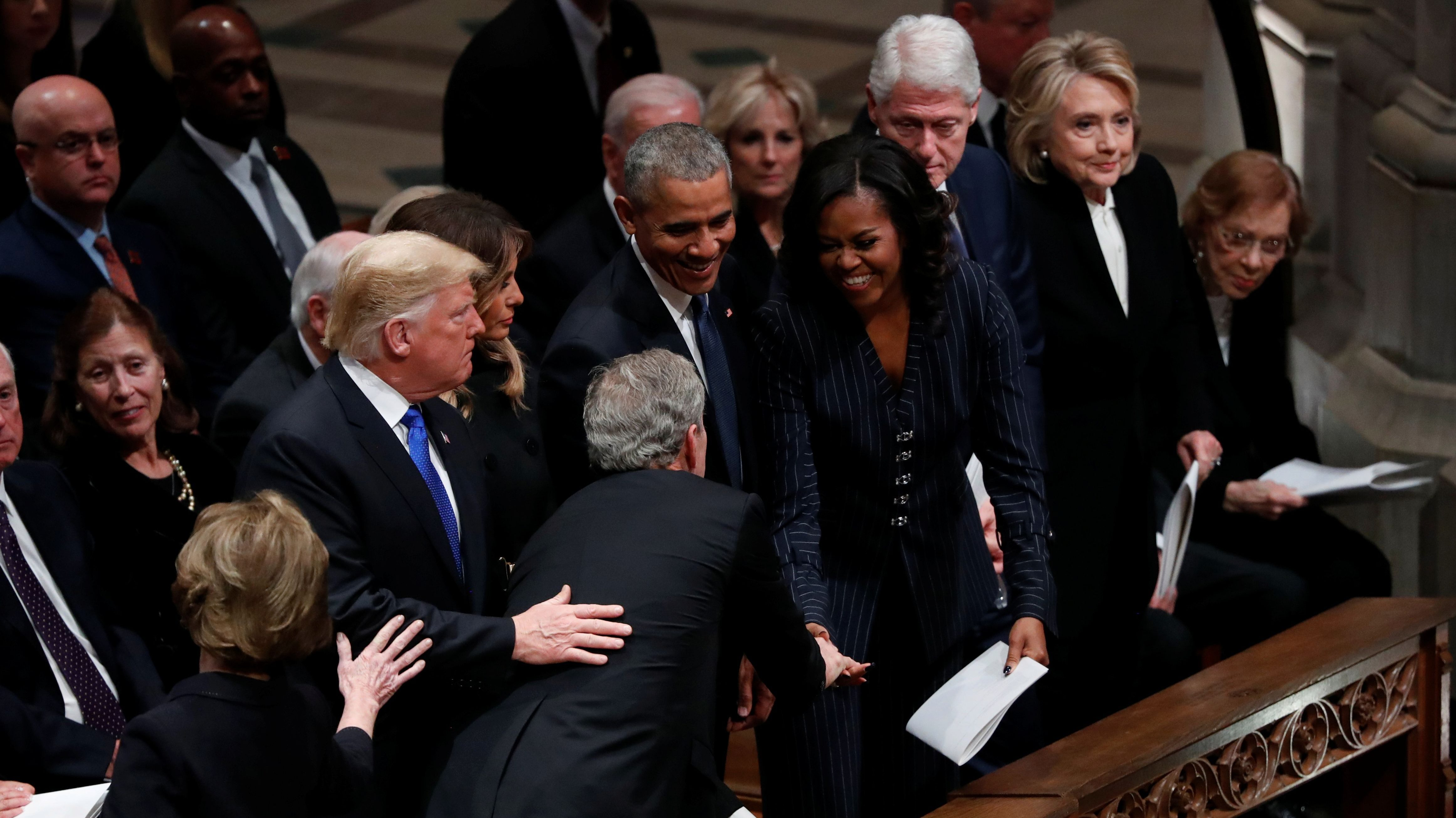 U.S. President George W. Bush reaches across in front of U.S. President Donald Trump and first lady Melania Trump to greet former President Barack Obama and former first lady Michelle Obama, sitting in the front row with former President Bill Clinton, former first lady Hillary Clinton and former first lady Rosalynn Carter as he arrives at the state funeral for his father former U.S. President George H.W. Bush at the Washington National Cathedral in Washington, U.S., December 5, 2018. REUTERS/Kevin Lamarque - RC1565D4EE00