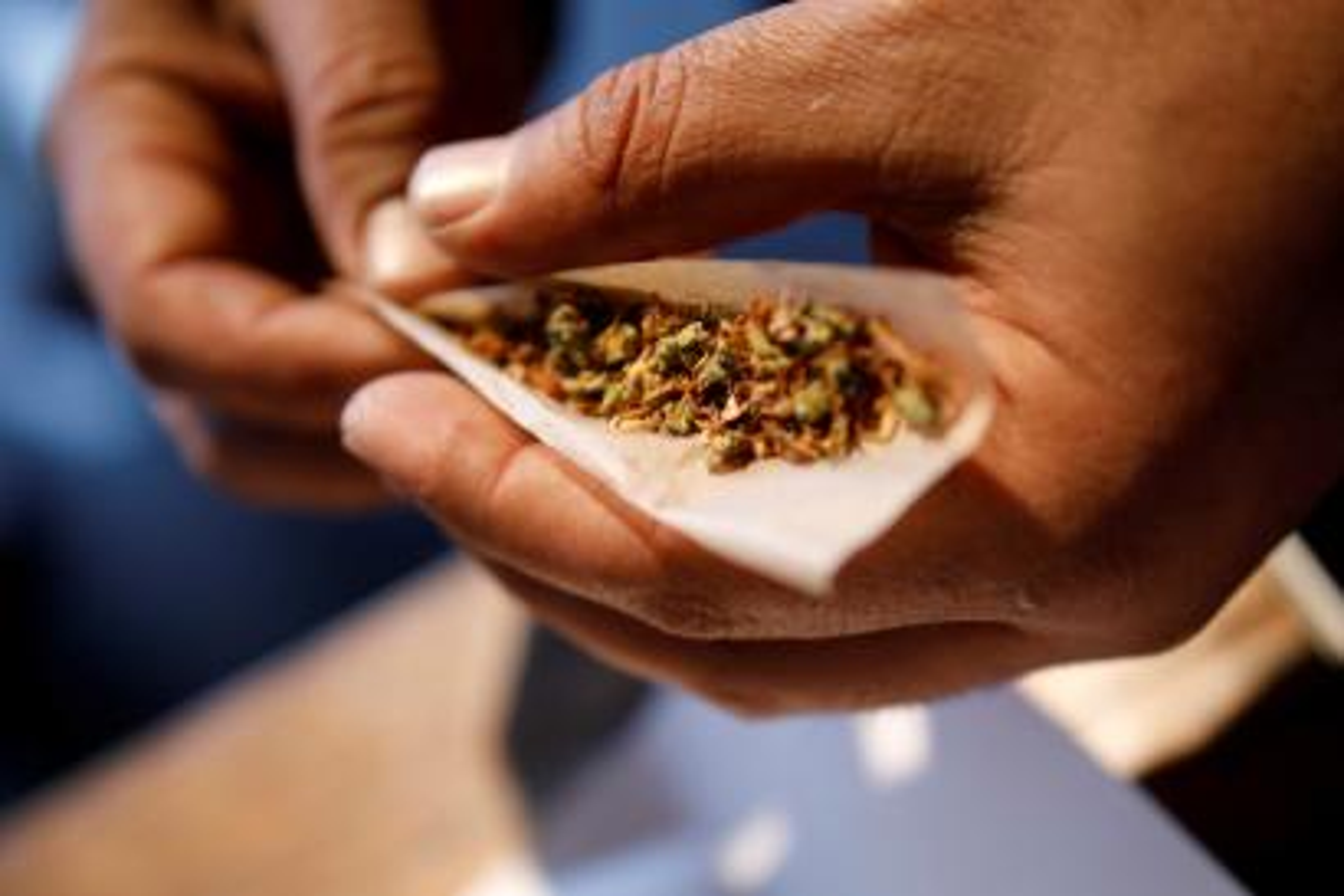A man rolls a joint.