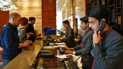 Receptionists attend to guests at their counter inside the Crown Plaza hotel, run by IHG, in New Delhi