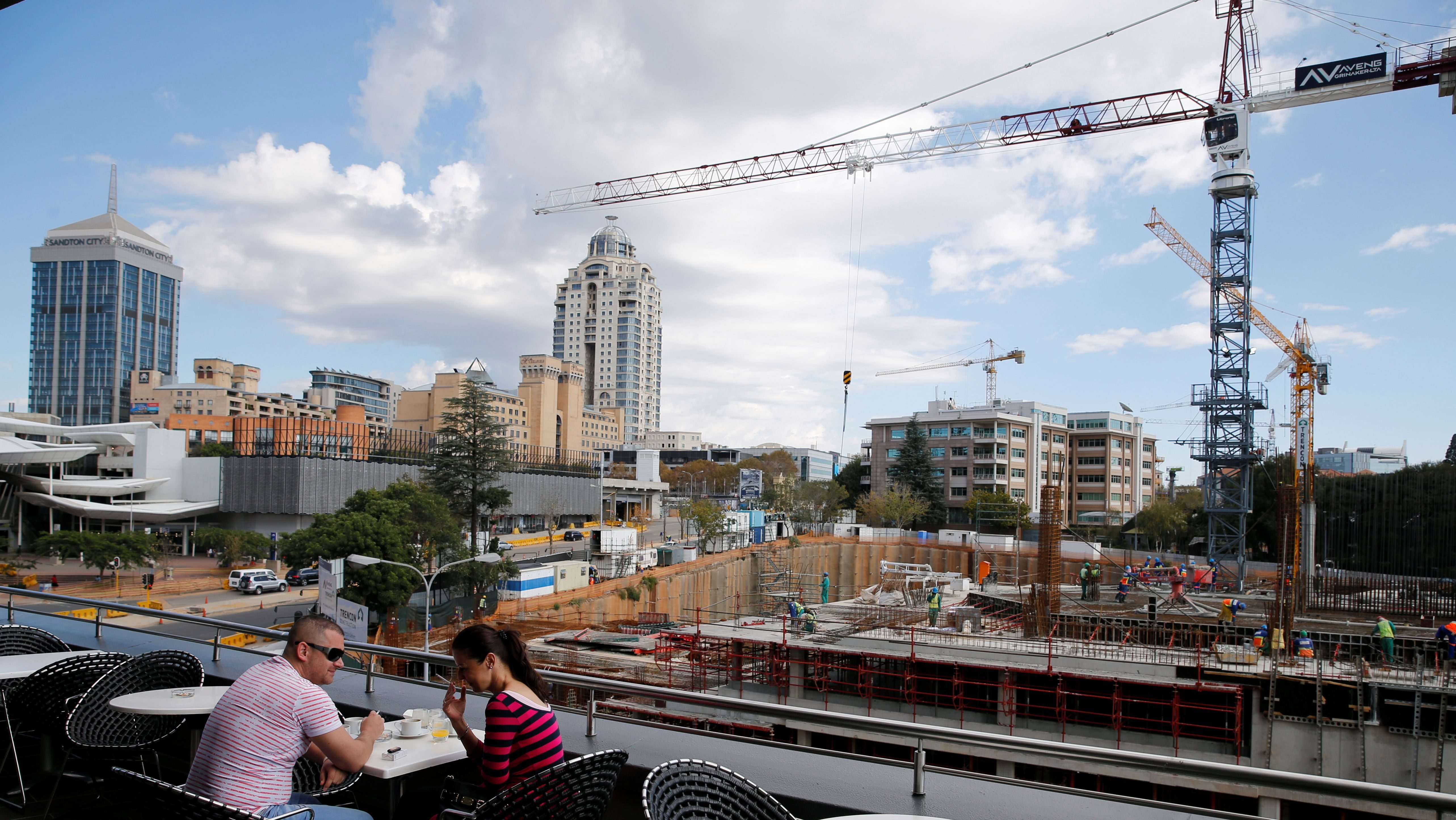 A couple is seen at a hotel balcony as construction takes place below the skyline of Johannesburg's upmarket Sandton suburb,April 23,2016.