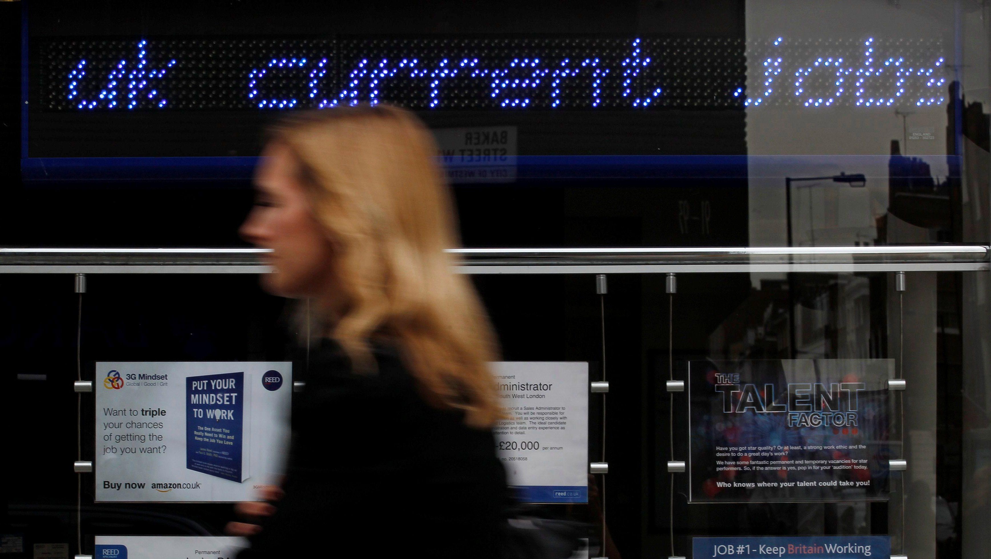 A pedestrian walks past an employment center in London August 17, 2011.