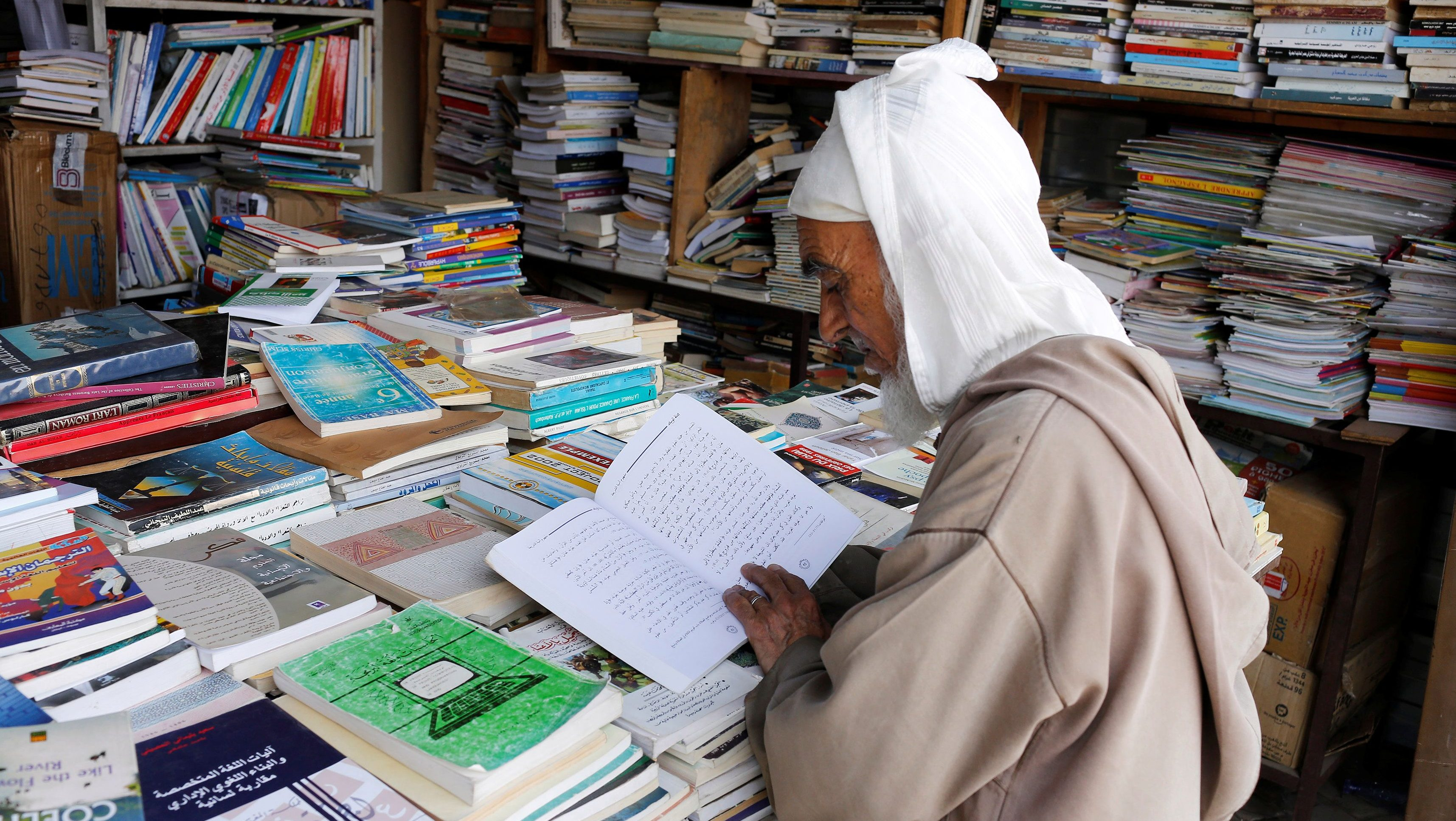 An elderly man reads a book in a bookshop in Bab Doukkala in the city of Marrakech, Morocco May 13, 2017. Picture taken May 13, 2017.