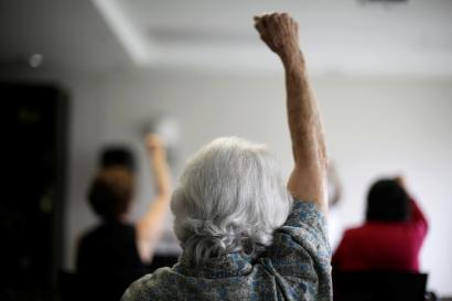 an elderly woman raises her hand