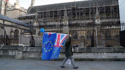 An anti-Brexit protester carries flags past the Houses of Parliament in London, Britain, December 11, 2018.