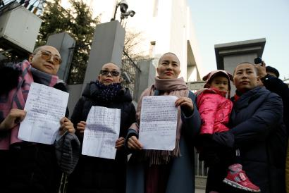 The wives of prominent Chinese rights lawyers Wang Qiaoling, Liu Ermin, Li Wenzu and Yuan Shanshan pose with petition letters they unsuccessfully tried to lodge at China's Supreme People's Court to protest their husband's treatment by the government in Beijing, China, December 17, 2018.