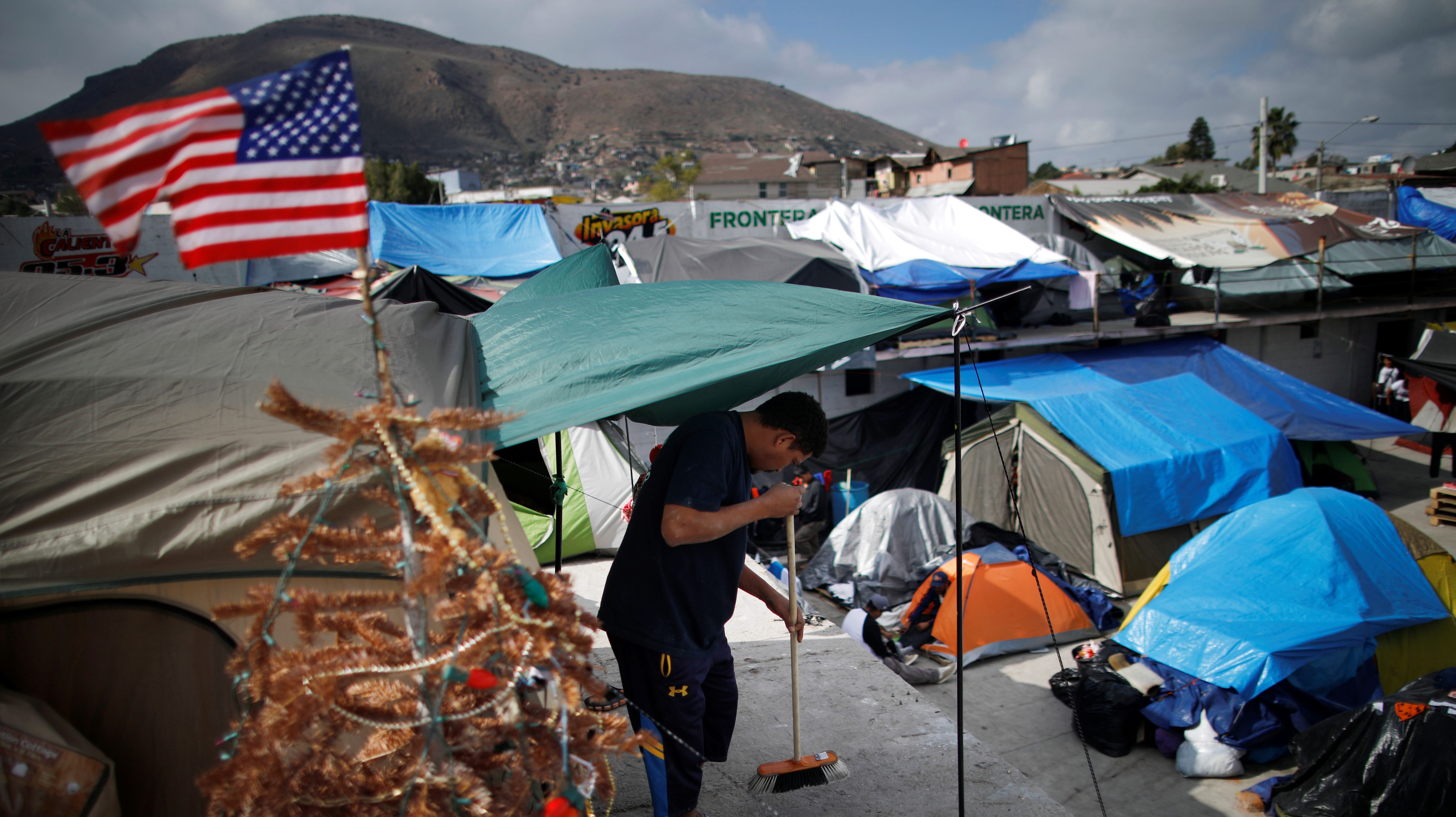 A U.S. flag and a Christmas tree are seen as Jose Calderon, part of a caravan of thousands from Central America trying to reach the United States, cleans the front of his tent at a temporary shelter in Tijuana, Mexico
