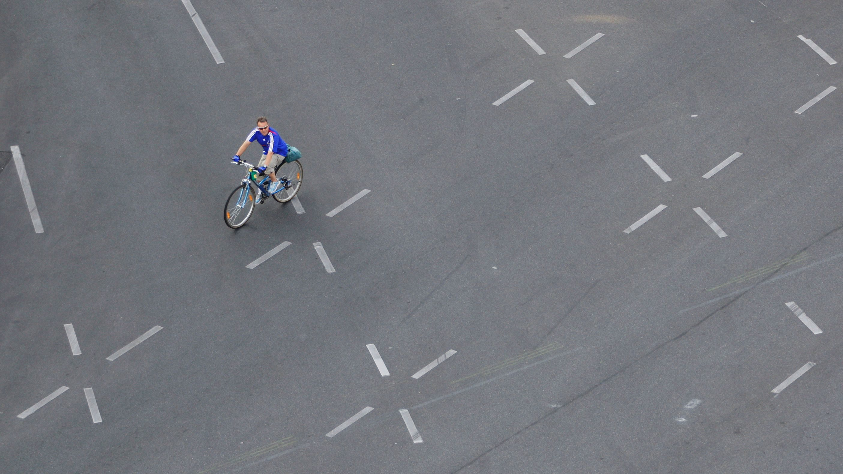A man on a bicycle drives over an empty street in front of victory column 'Siegessaeule' in Berlin