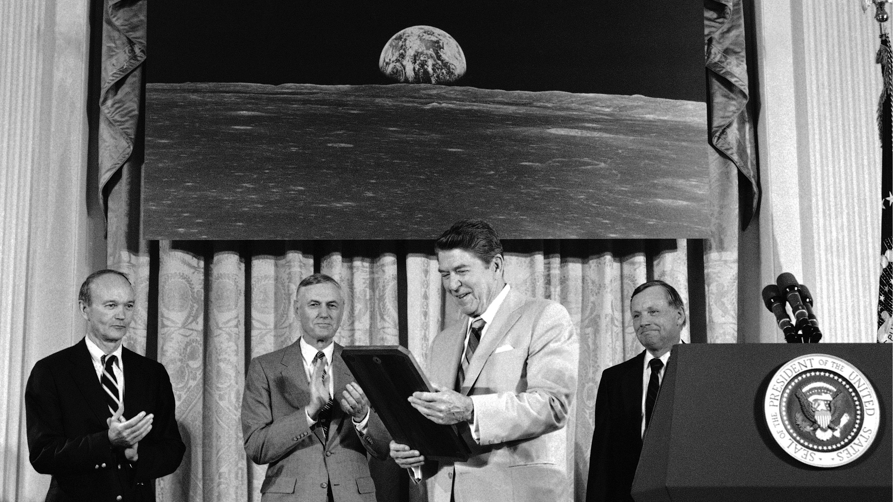 Pres. Ronald Reagan, center, admires a plaque he was presented by Apollo 11 astronauts during a ceremony at the White House on the 15th anniversary of their mission to the moon at the White House during a ceremony to proclaim Space Exploration Day, Friday, July 21, 1984, Washington, D.C. Behind the President, from left are, Michael Collins, NASA Administrator James Beggs; Reagan; and Neil Armstrong.