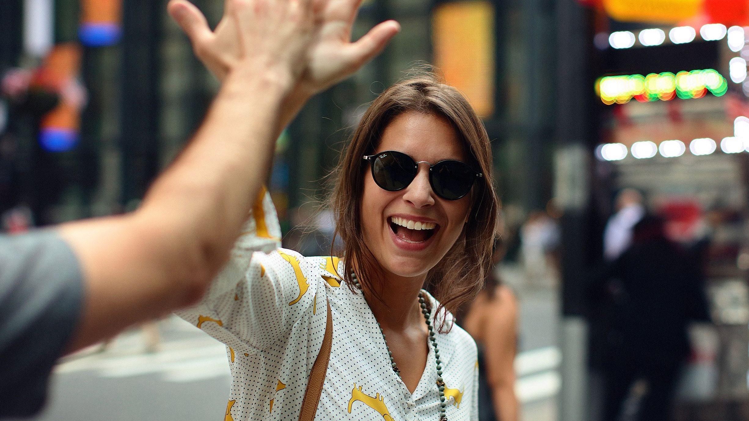 A smiling woman high fives a man