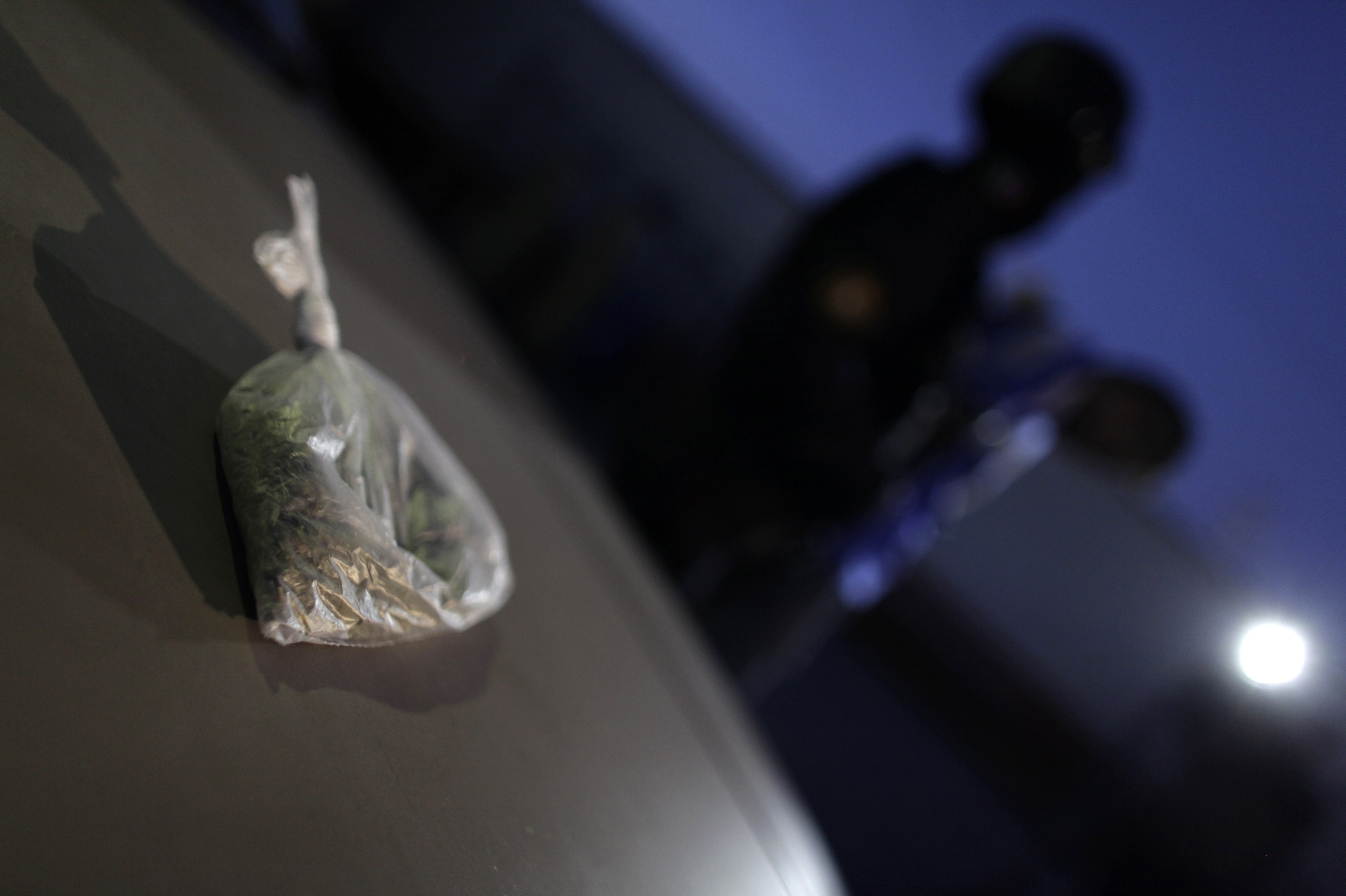 A bag of marijuana is on display as suspects are presented to the media after their arrest in Monterrey December 30, 2011. The two suspects were arrested after police found a small bag with marijuana valued at approximately 500 pesos ($36) in their car during a routine check, according to local media. (MEXICO - Tags: CRIME LAW DRUGS SOCIETY) - GM1E7CV15O601