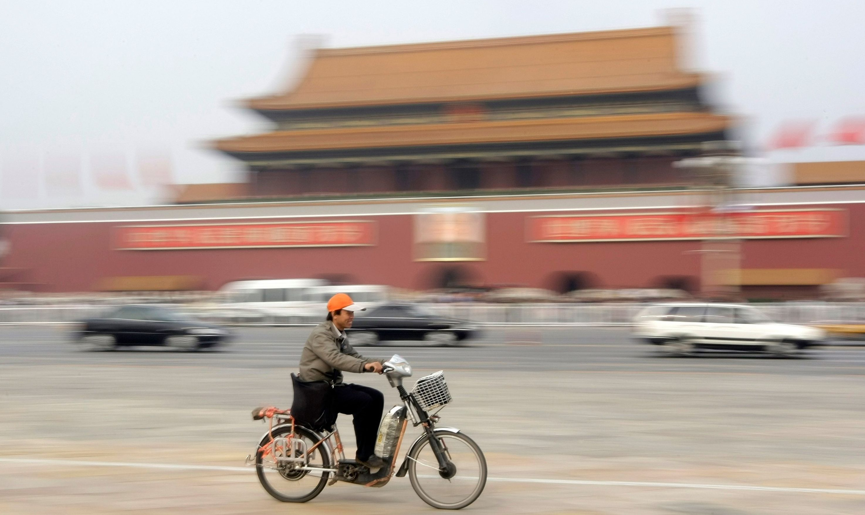 A man rides an electric bicycle past Beijing's Tiananmen Gate, October 21, 2008.