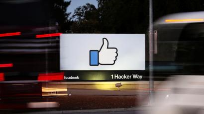 The entrance sign to Facebook headquarters is seen through two moving buses in Menlo Park, California, on Wednesday, October 10, 2018.