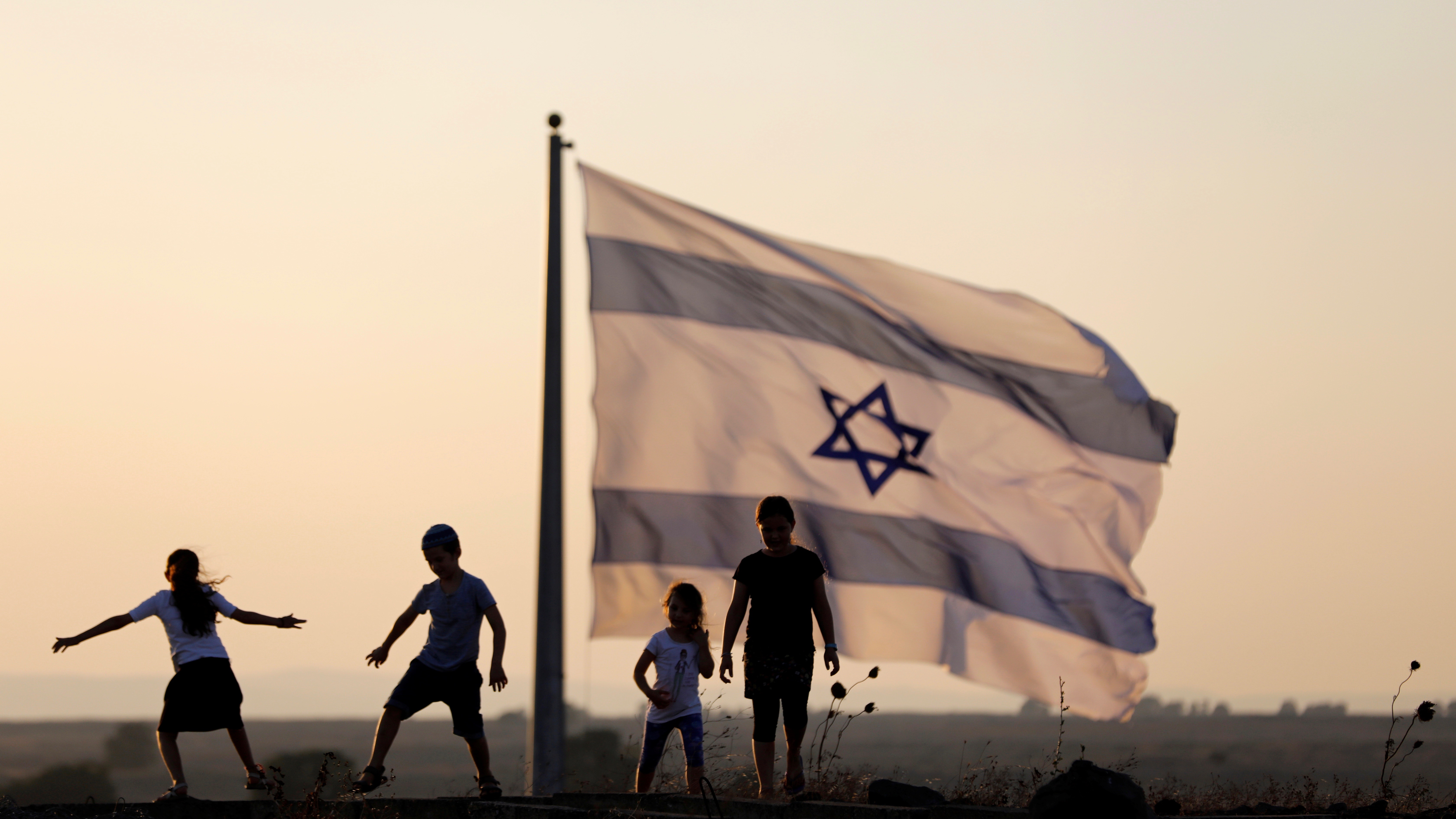 Israeli kids play next to an Israeli flag next to the Israeli Syrian border.