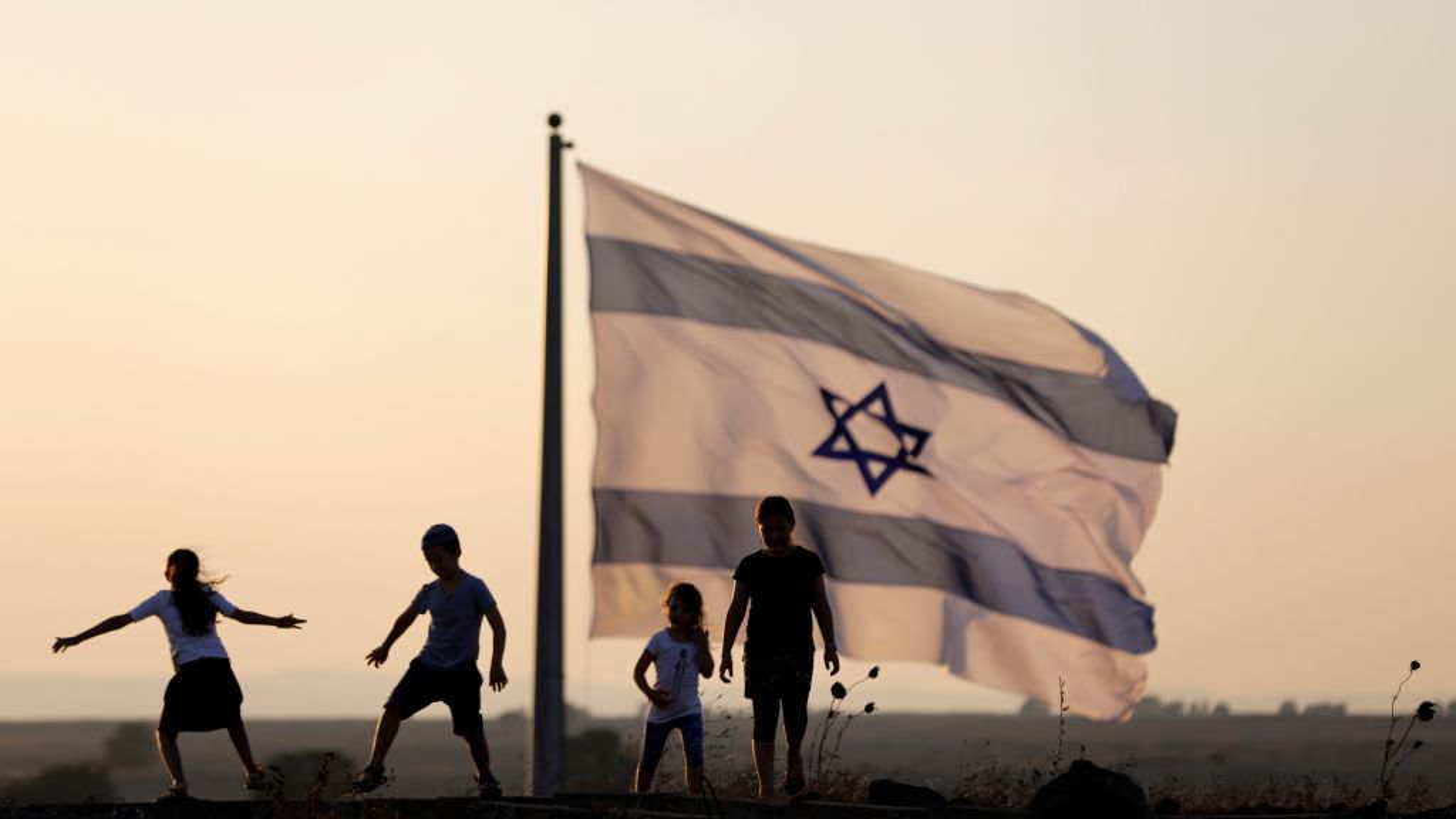 Israeli kids play next to an Israeli flag next to the Israeli Syrian border.