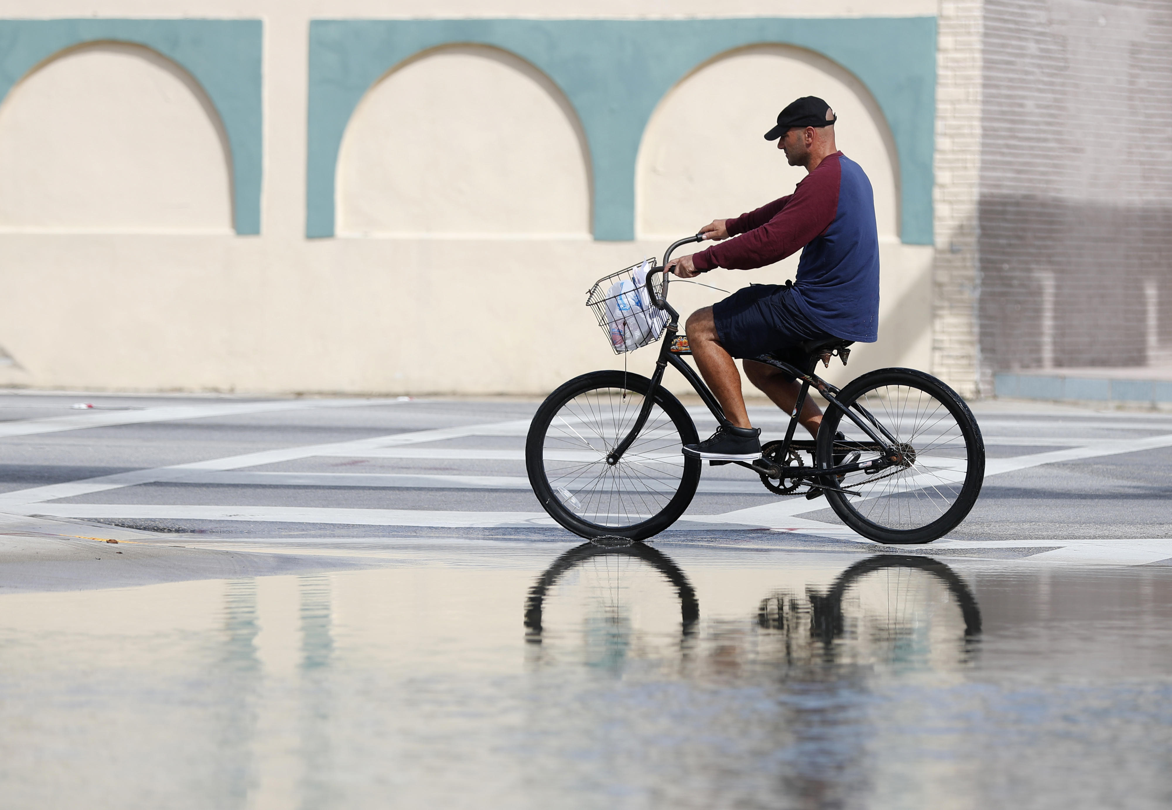 A cyclist rides past an area flooded during a King Tide, an especially high tide, Tuesday, Oct. 9, 2018, in Miami.