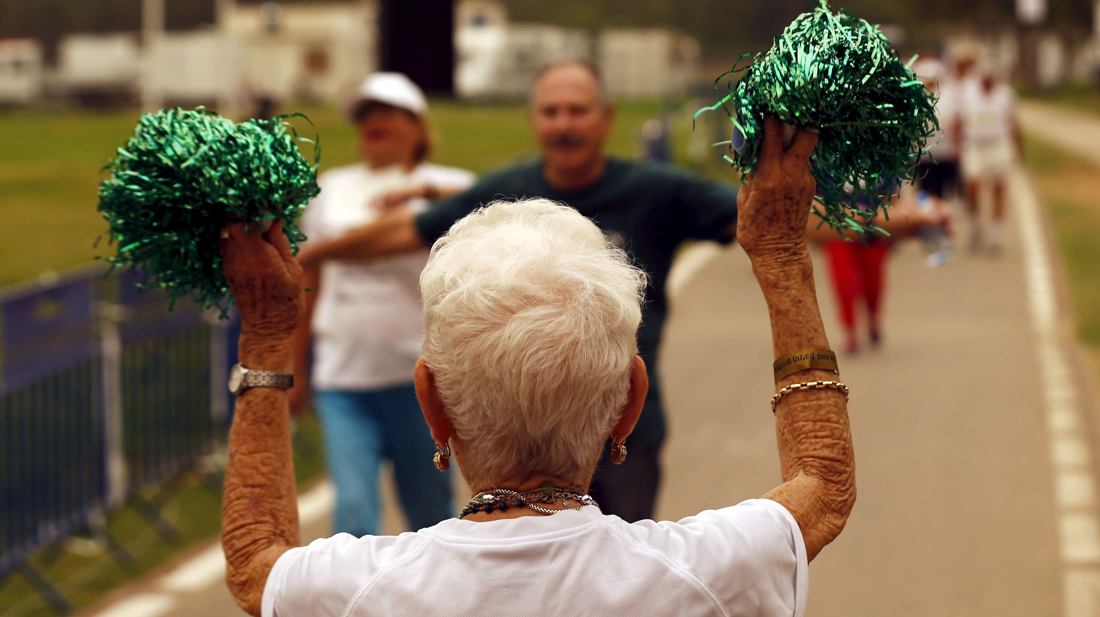 A senior woman cheers as others take part in games for people over 65 years old, organized by a nursing home in Tel Aviv, Israel.