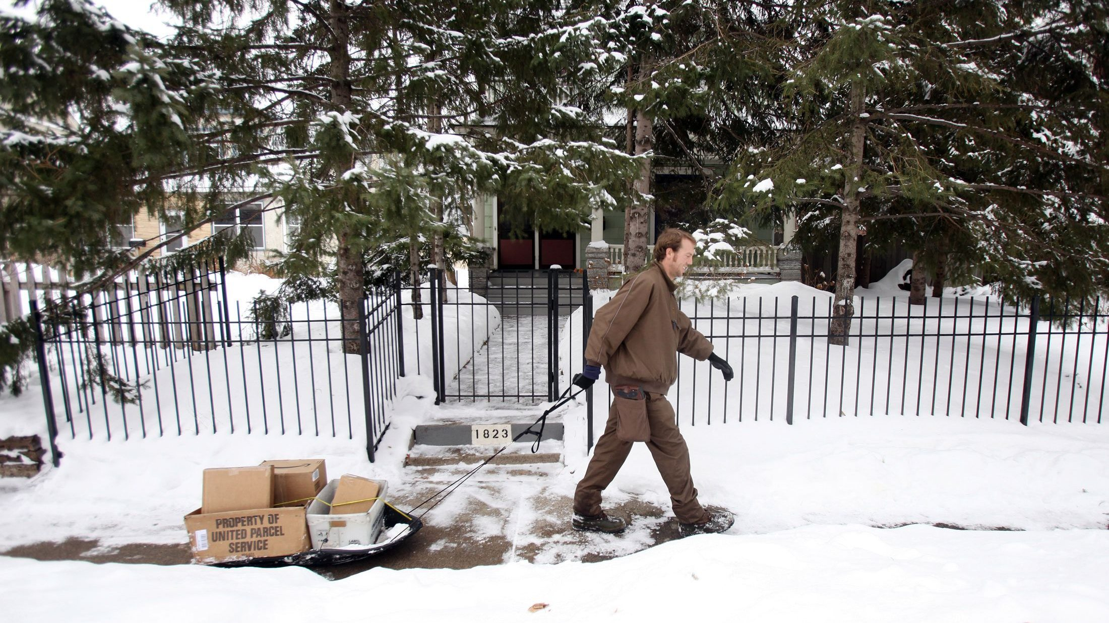 United Parcel Service worker Ryan Hewitt uses a sled to make deliveries through snowy conditions in Minneapolis, December 22, 2010. Today is the busiest delivery day of the year for UPS.