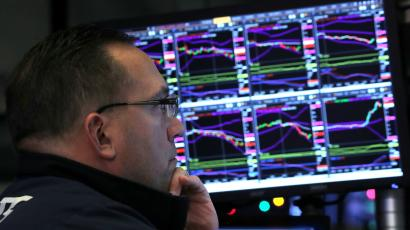 A trader looks at price monitors as he works on the floor at the New York Stock Exchange (NYSE) in New York City
