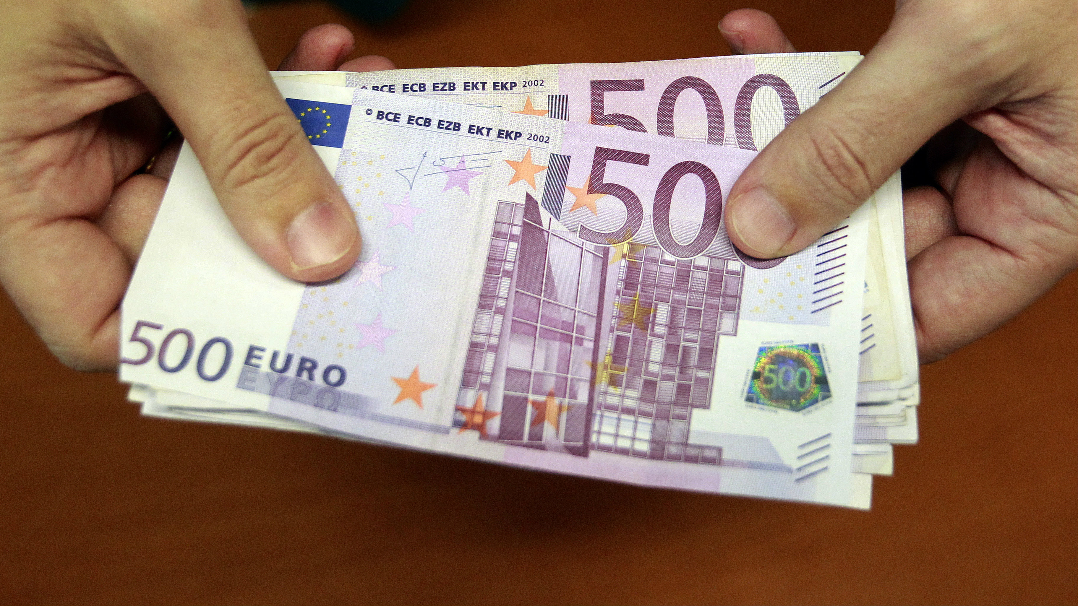 A bank employee holds a pile of 500 euro notes