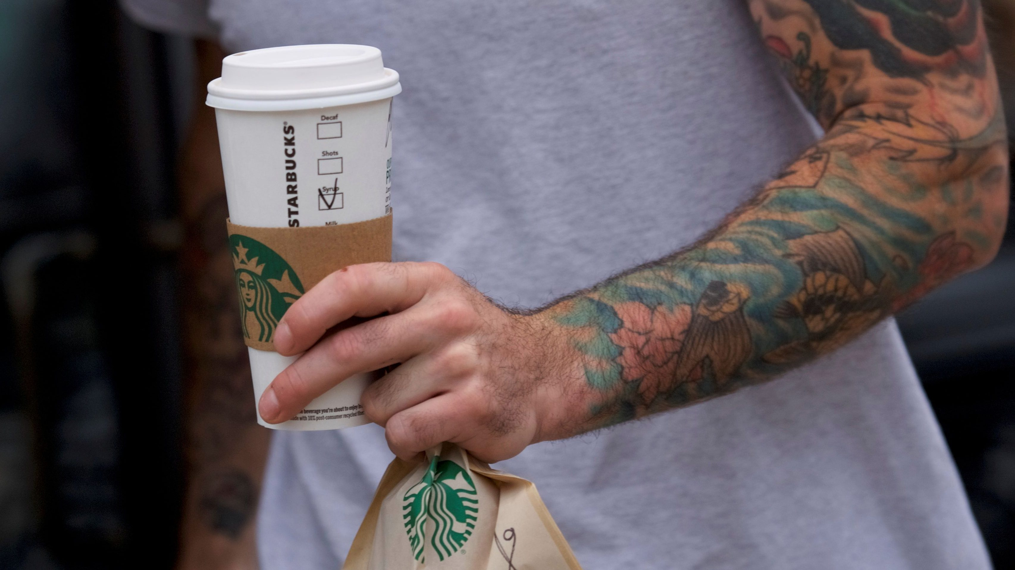 A man exits a Center City Starbucks clutching a hot beverage and bag of food