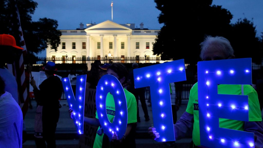 "Protestors hold up letters spelling ""VOTE"" outside of the White House in Washington."