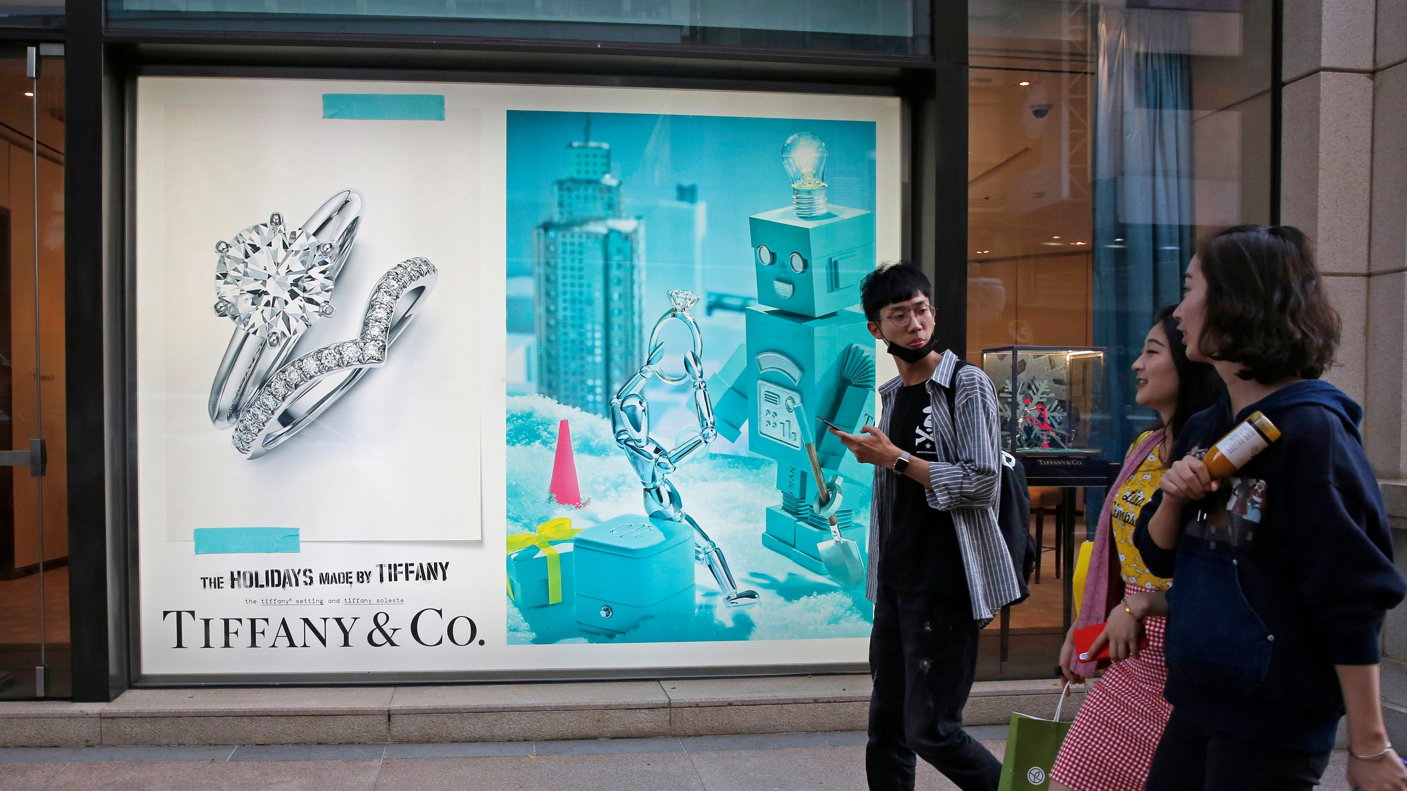 In this Thursday, Nov. 29, 2018 photo, Chinese tourists walk past a Tiffany & Co. flagship in Canton Road, the one-stop-shop high street of high-end brands in Hong Kong. The designer boutiques of Manhattan and Paris are feeling the chill of a Chinese economic slowdown that has hammered automakers and other industries. That is jolting brands such as Louis Vuitton and Burberry that increasingly rely on Chinese customers who spend $90 billion a year on jewelry, clothes and other high-end goods. The industry already is facing pressure to keep up as China's big spenders shift to buying more at the spreading networks of luxury outlets in their own country. (AP Photo/Kin Cheung)