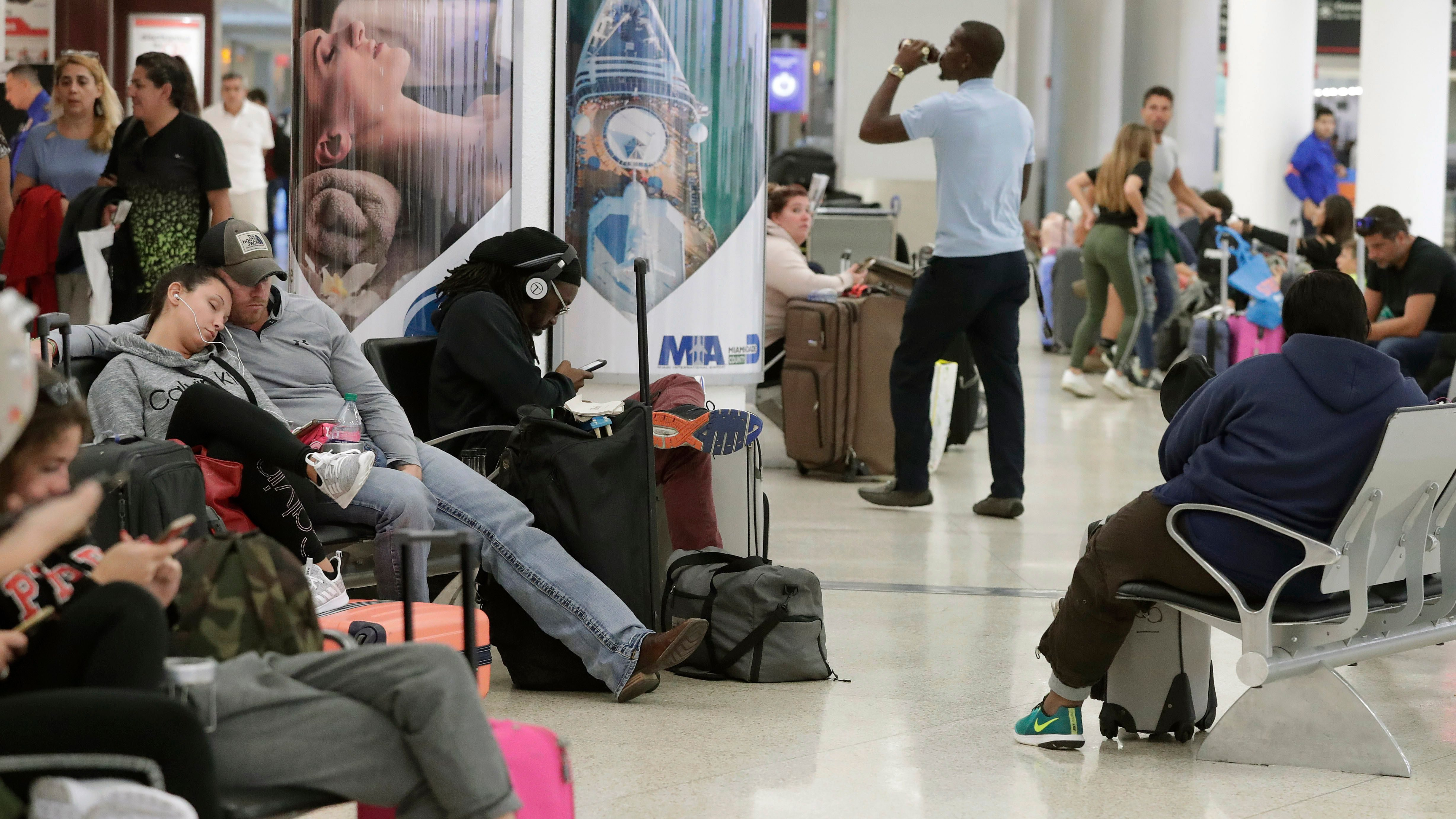 Travelers wait near a closed down terminal at the Miami International Airport on Saturday, Jan. 12, 2019, in Miami. The partial government shutdown is starting to strain the national aviation system, with unpaid security screeners staying home, air-traffic controllers suing the government and safety inspectors off the job. (AP Photo/Brynn Anderson)