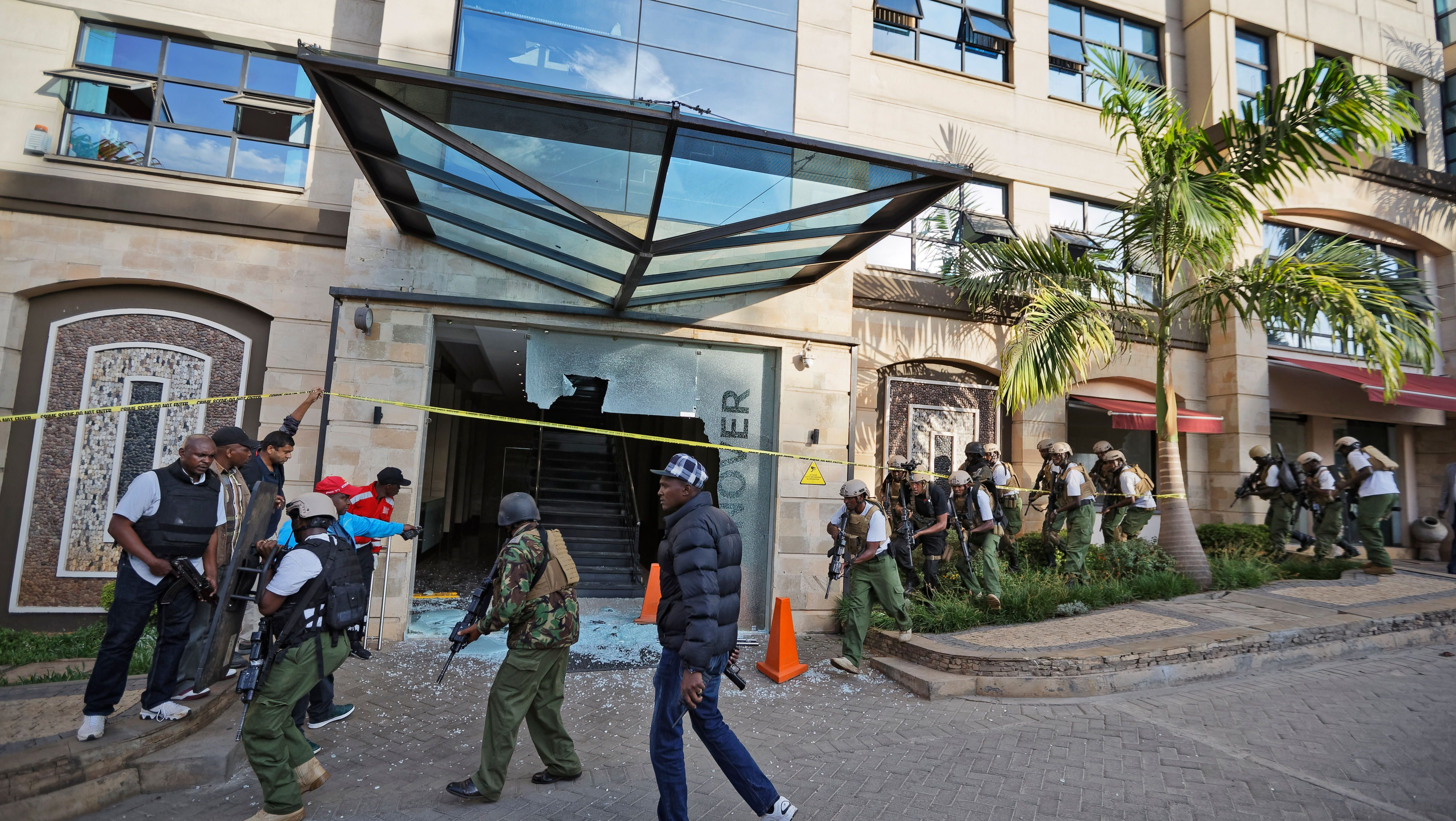 Security forces surround a hallway behind a shattered door in which an unexploded grenade lies, at a hotel complex in Nairobi, Kenya Tuesday, Jan. 15, 2019. Terrorists attacked an upscale hotel complex in Kenya's capital Tuesday, sending people fleeing in panic as explosions and heavy gunfire reverberated through the neighborhood.