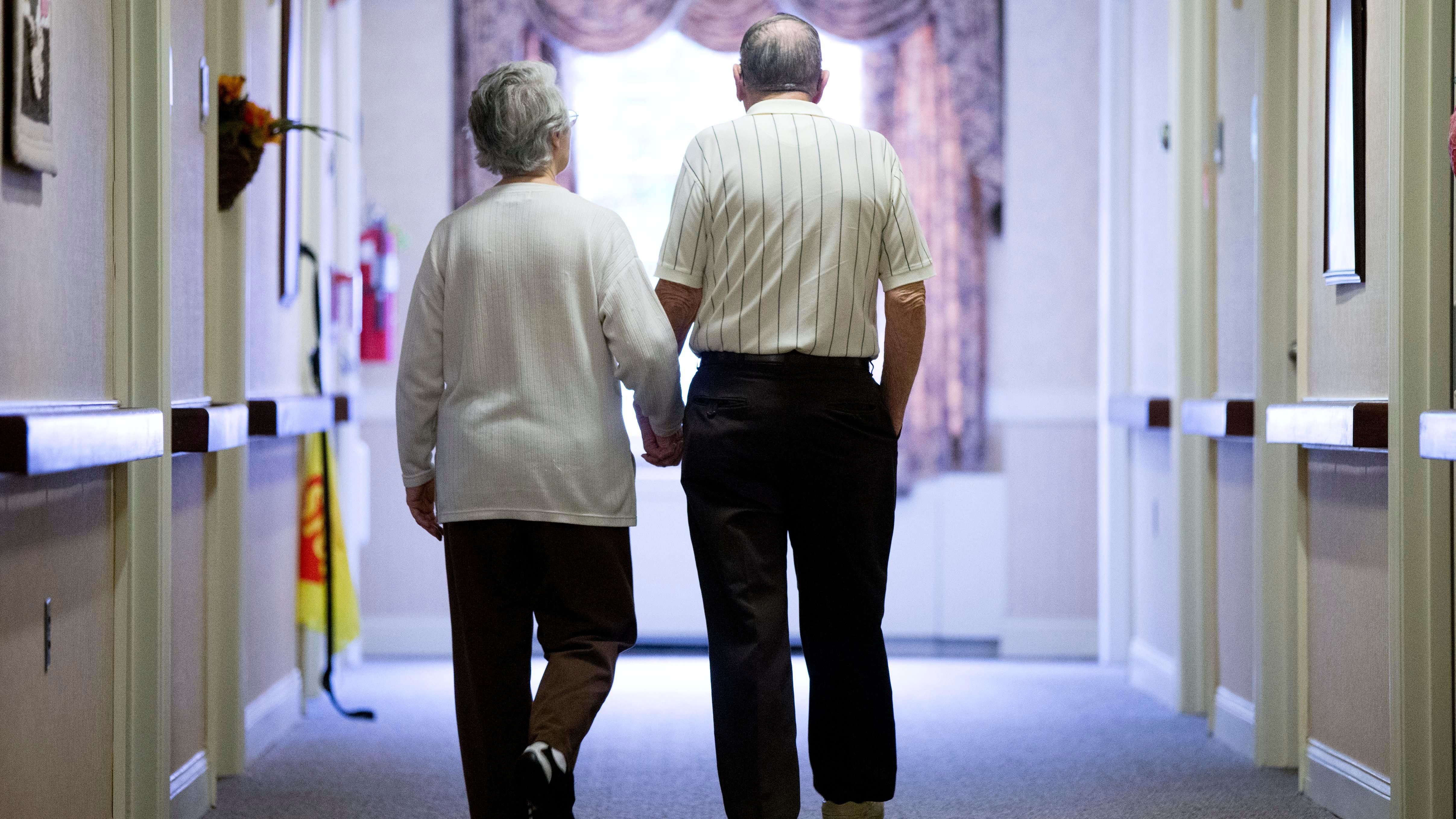 An elderly couple walking down a hallway.