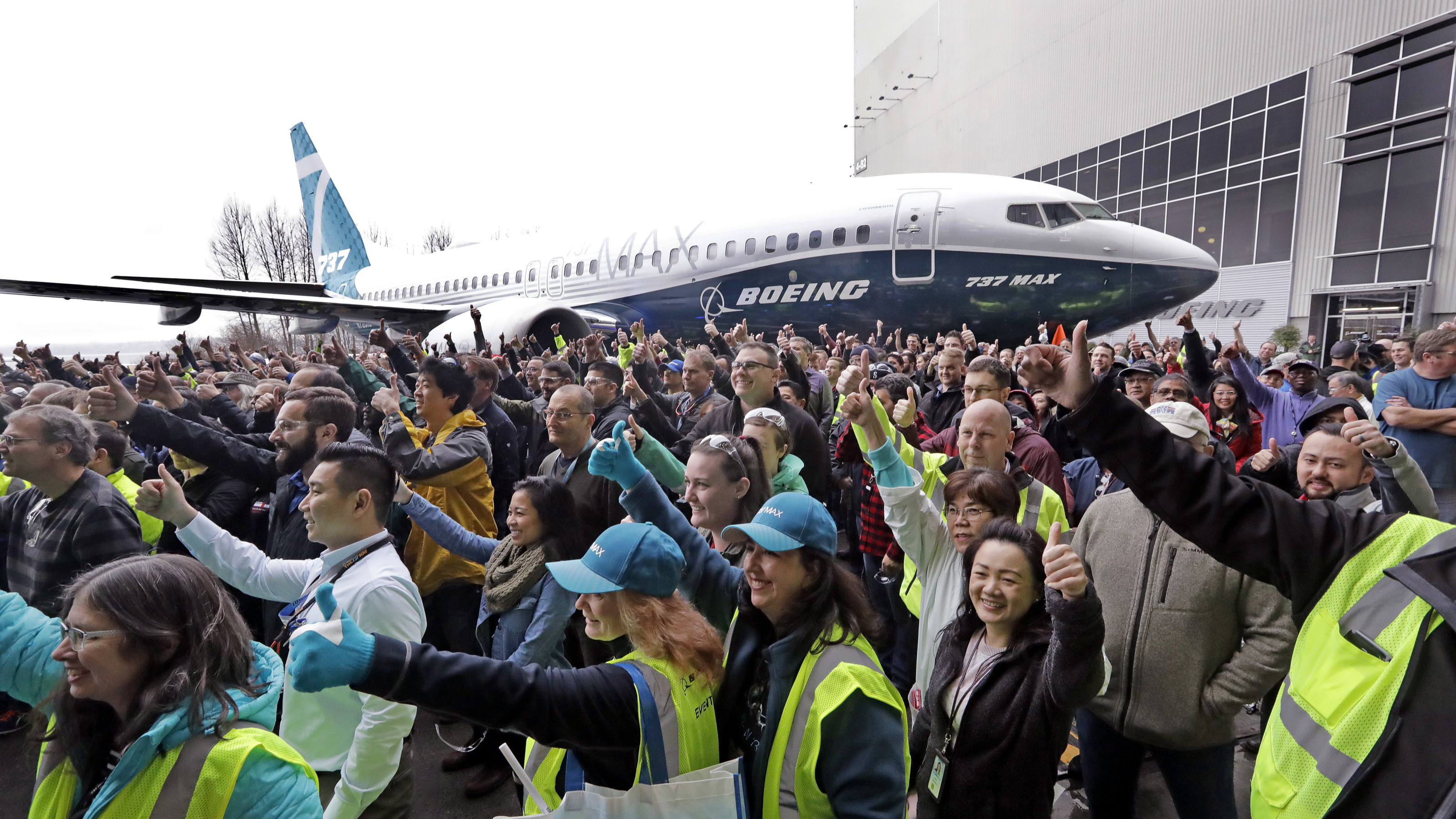Boeing workers pose in front of a Boeing 737 MAX 7, the newest version of Boeing's fastest-selling airplane, for a group photo during a debut for employees and media of the new jet Monday, Feb. 5, 2018, in Renton, Wash. The company says that the airplane improves on the design of its predecessor, the 737-700, with more capability, range and seats. Following upcoming flight tests, it is expected to be delivered to airline customers beginning in 2019.