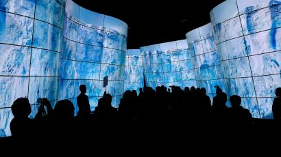 People walk through a display of television screens during CES International, Tuesday, Jan. 9, 2018, in Las Vegas.