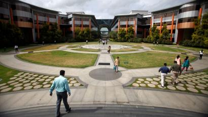 Employees walk in a forecourt at the Infosys campus in the Electronic City area of Bangalore