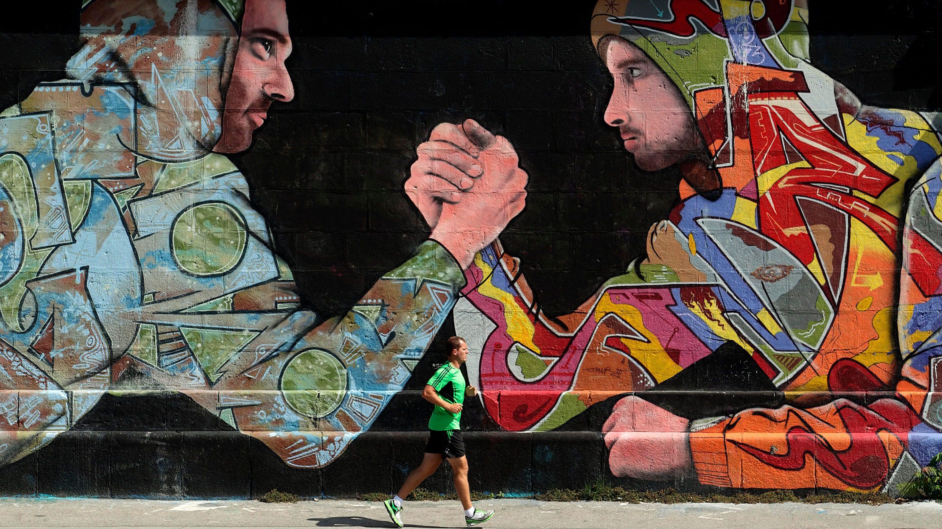 A jogger runs past graffiti on a sunny summer day in Vienna