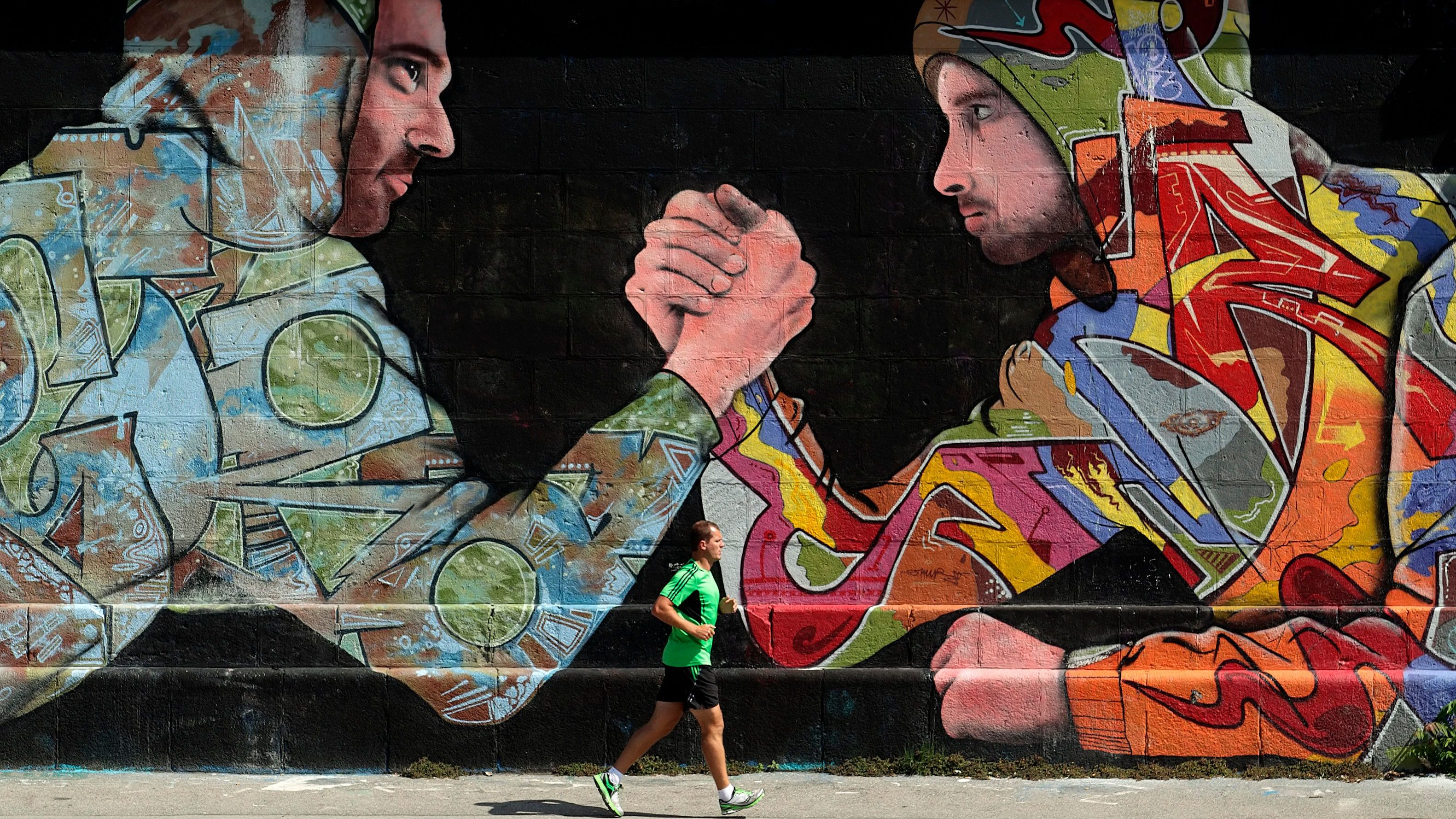 A jogger runs past graffiti on a sunny summer day in Vienna