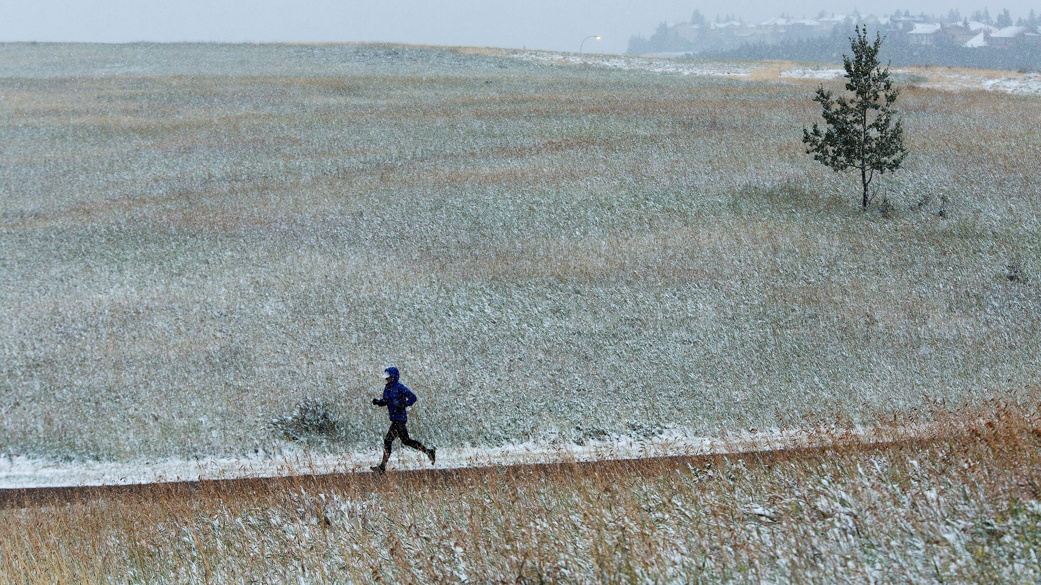 A jogger runs through the snow at Nose Hill Park during an early year snow fall in Calgary