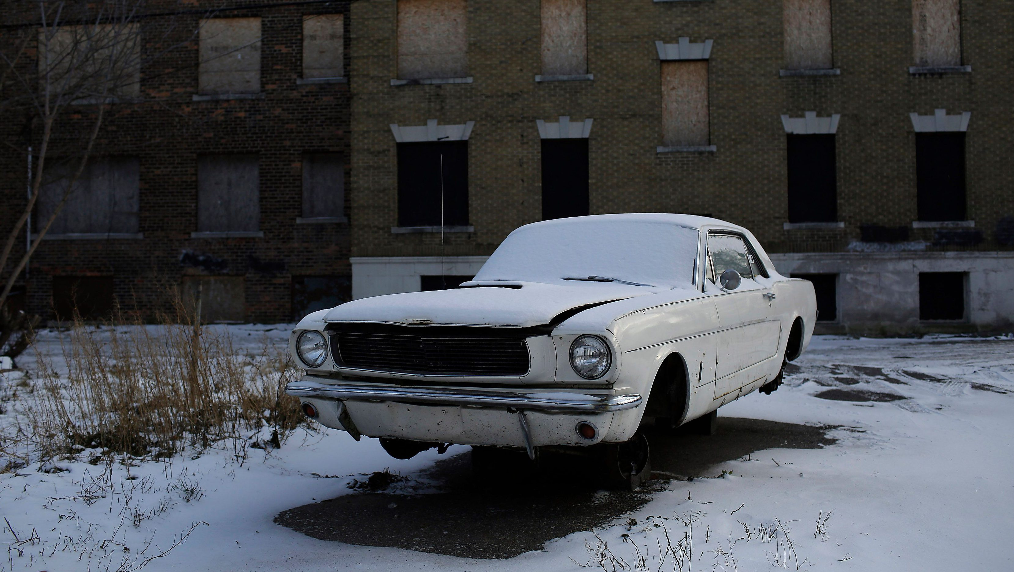 An older model Ford Mustang sits on cinder blocks with missing wheels near an abandoned apartment building in Detroit, Michigan January 7, 2015. Detroit, also known as the Motor City, is the historic hub of automobile manufacturing in the United States. A federal judge in December 2013 formally declared the city bankrupt but it won court approval to exit bankruptcy last November. Once the proud symbol of U.S. industrial strength, Detroit fell on hard times after decades of population loss, rampant debt and financial mismanagement left it struggling to provide basic services to residents. The Detroit car show, formally the North American International Auto Show, is being held for the 26th year and represents the turn in the city's fortune with 2014 being the best year for U.S. car sales since 2006. Reuters photographer Joshua Lott documented old or damaged cars, a common element in a series of cityscapes in the former automobile industry giant. REUTERS/Joshua Lott (UNITED STATES - Tags: TRANSPORT CITYSCAPE SOCIETY BUSINESS TPX IMAGES OF THE DAY) ATTENTION EDITORS: PICTURE 01 OF 16 FOR WIDER IMAGE PACKAGE 'WRECKED IN DETROIT' TO FIND ALL IMAGES SEARCH 'CITYSCAPES LOTT' - LM2EB1D0JVA01