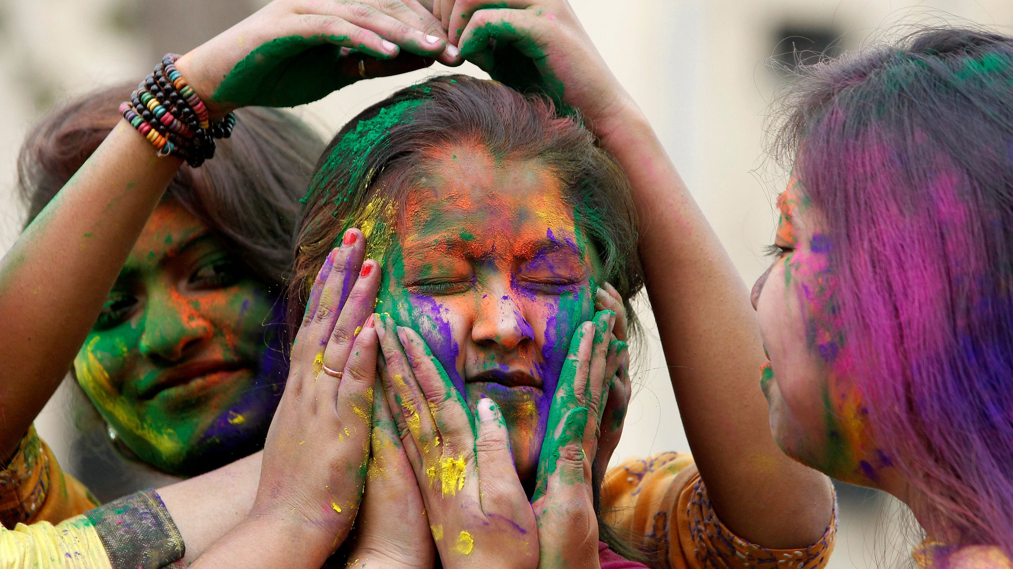 A college student reacts as others apply coloured powder on her face during Holi, the Festival of Colours, celebrations in Agartala
