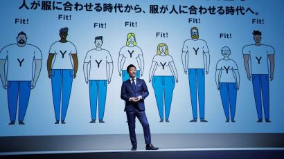 Yusaku Maezawa, the chief executive of Zozo, which operates Japan's popular fashion shopping site Zozotown and is officially called Start Today Co, speaks in front of a projection about Zozosuit at an event launching the debut of its formal apparel items, in Tokyo, Japan, July 3, 2018. Picture taken July 3, 2018. REUTERS/Kim Kyung-Hoon - RC1578C27420